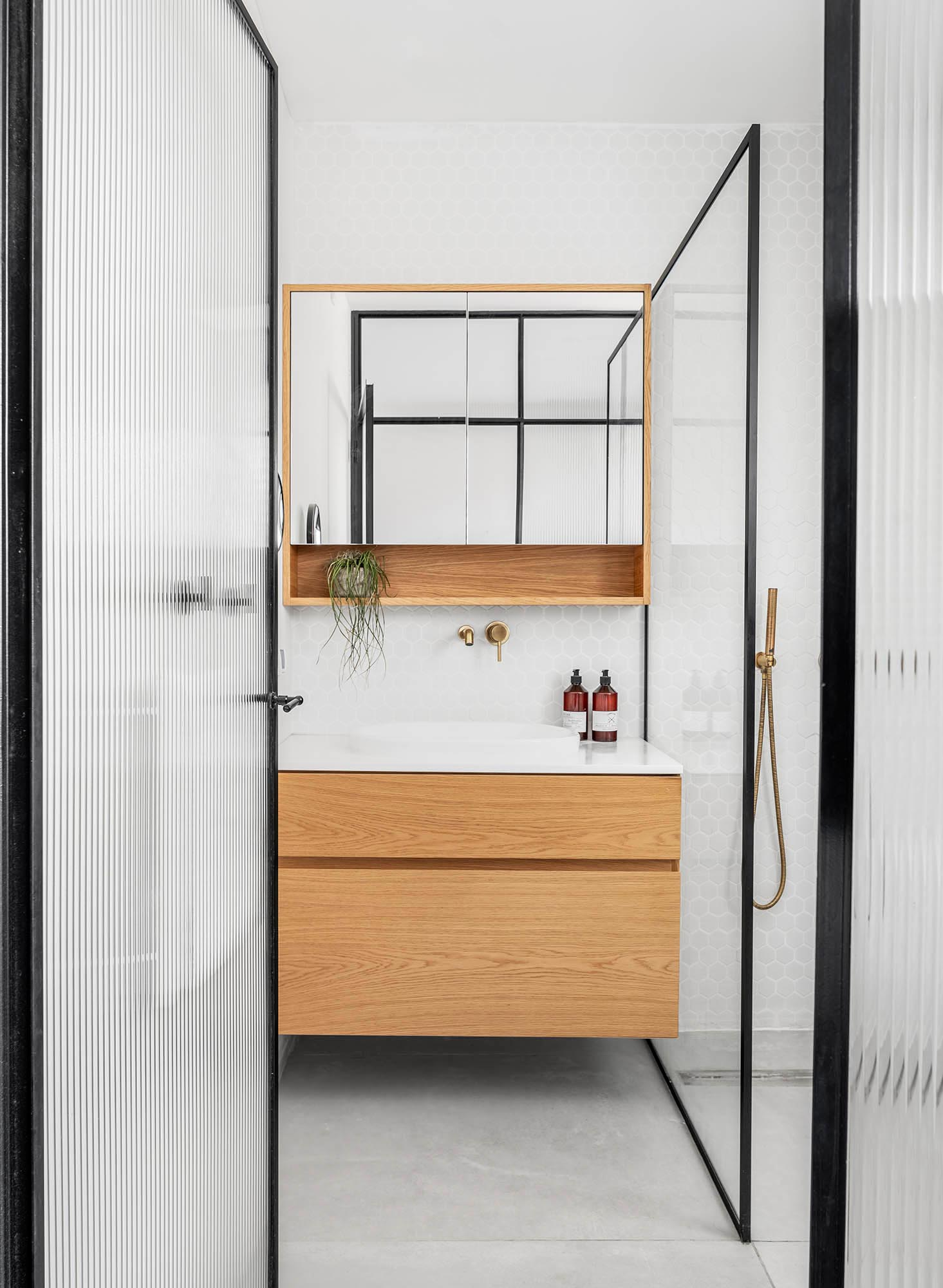 Inside this modern bathroom is a floating wood vanity with a white countertop and sink, while white hexagonal tiles cover the walls.