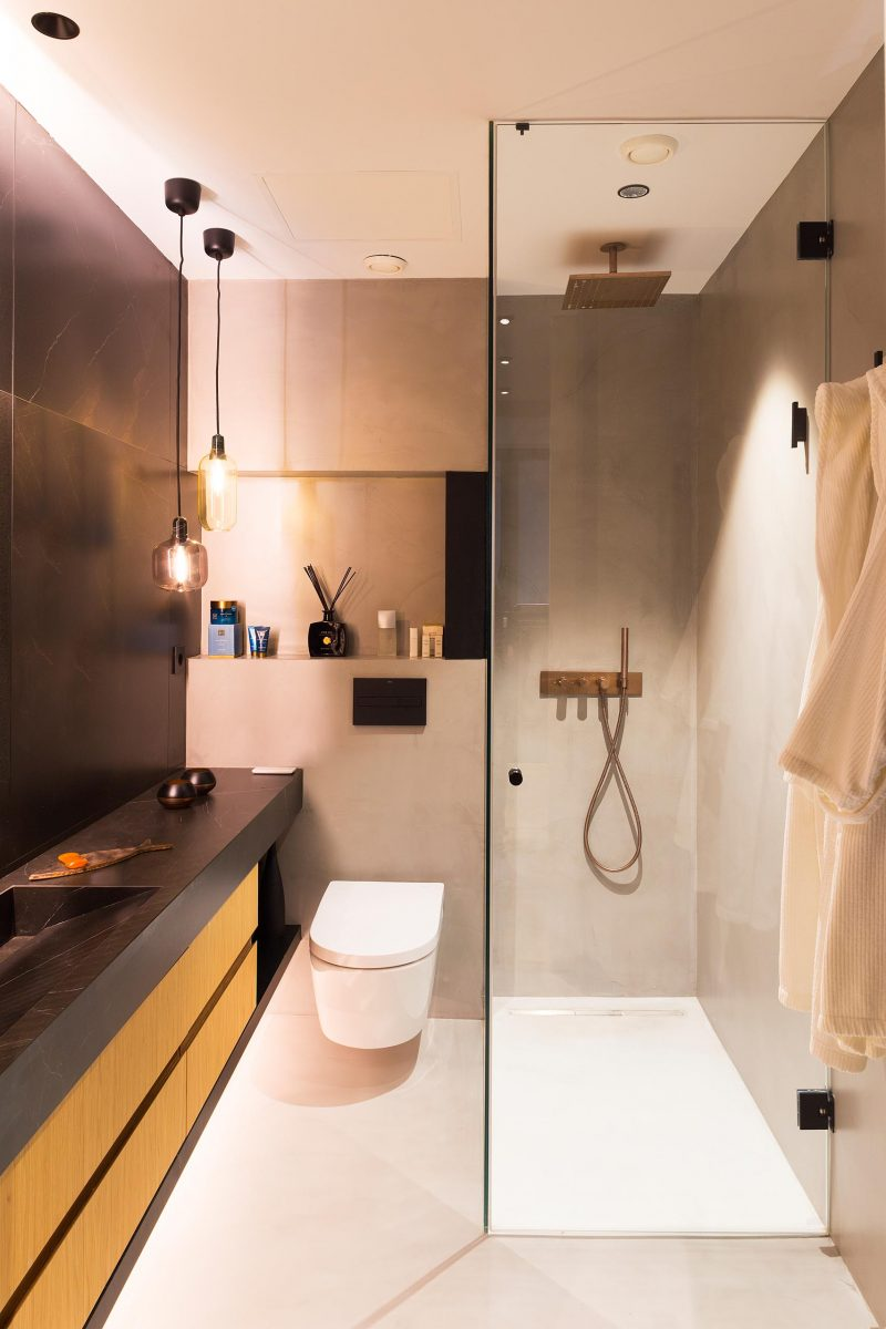 A modern bathroom with a black and wood vanity, a glass enclosed shower, and a shelving nice.