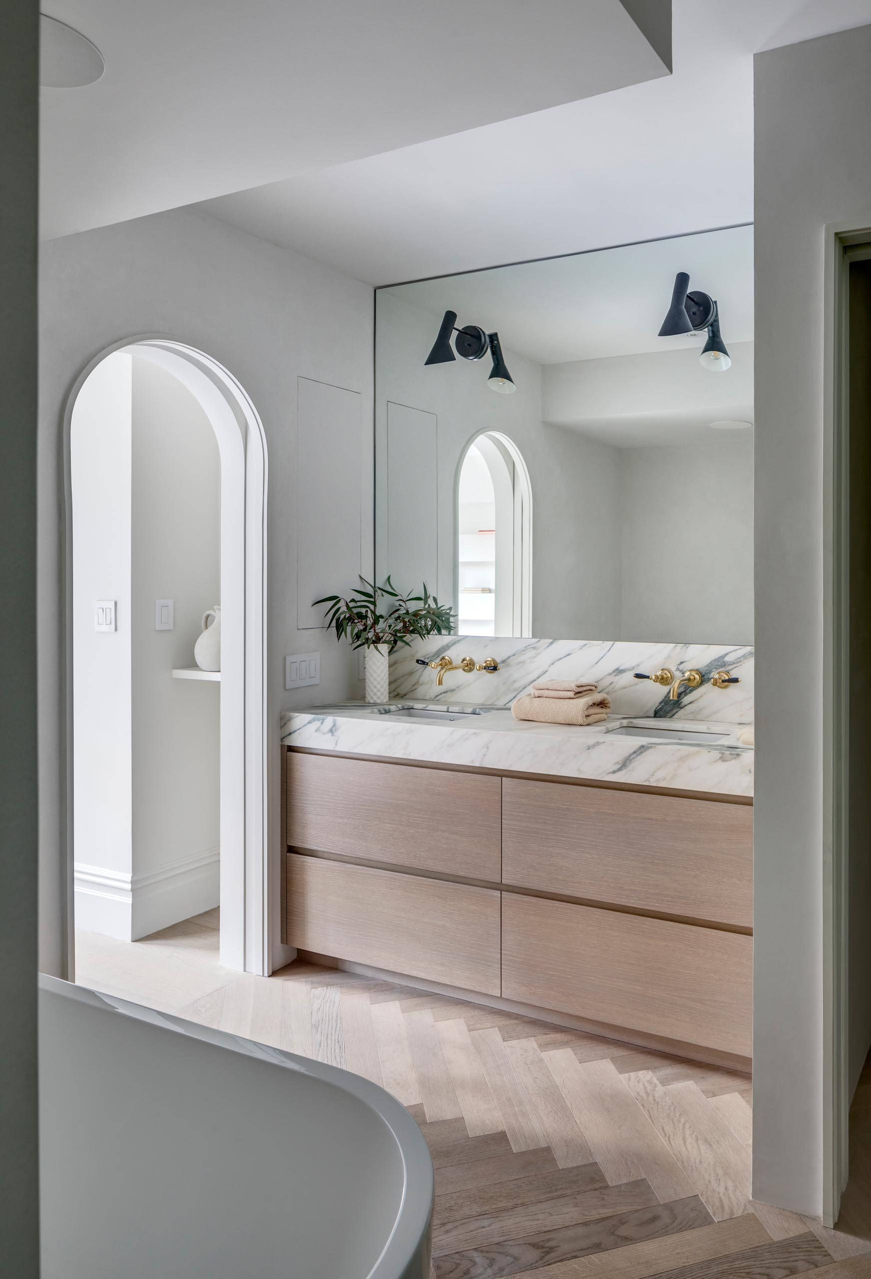 A modern master bathroom with an arched doorway, a wood and marble vanity, and a wood floor laid in a herringbone pattern.