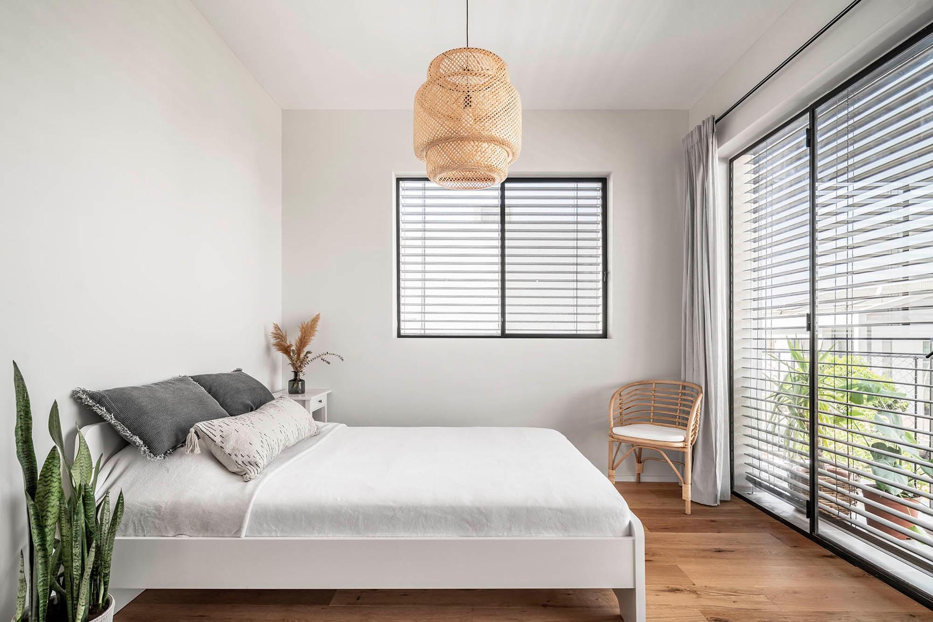 This modern bedroom is simple and bright with light-colored walls, wooden accents, and plants.