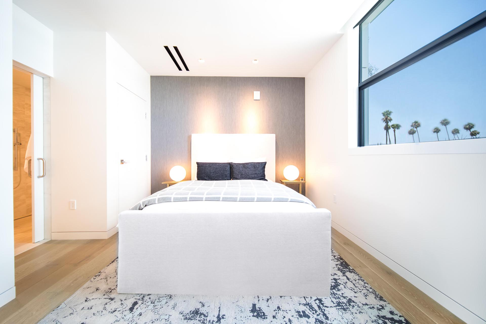 A modern bedroom with a gray accent wall.