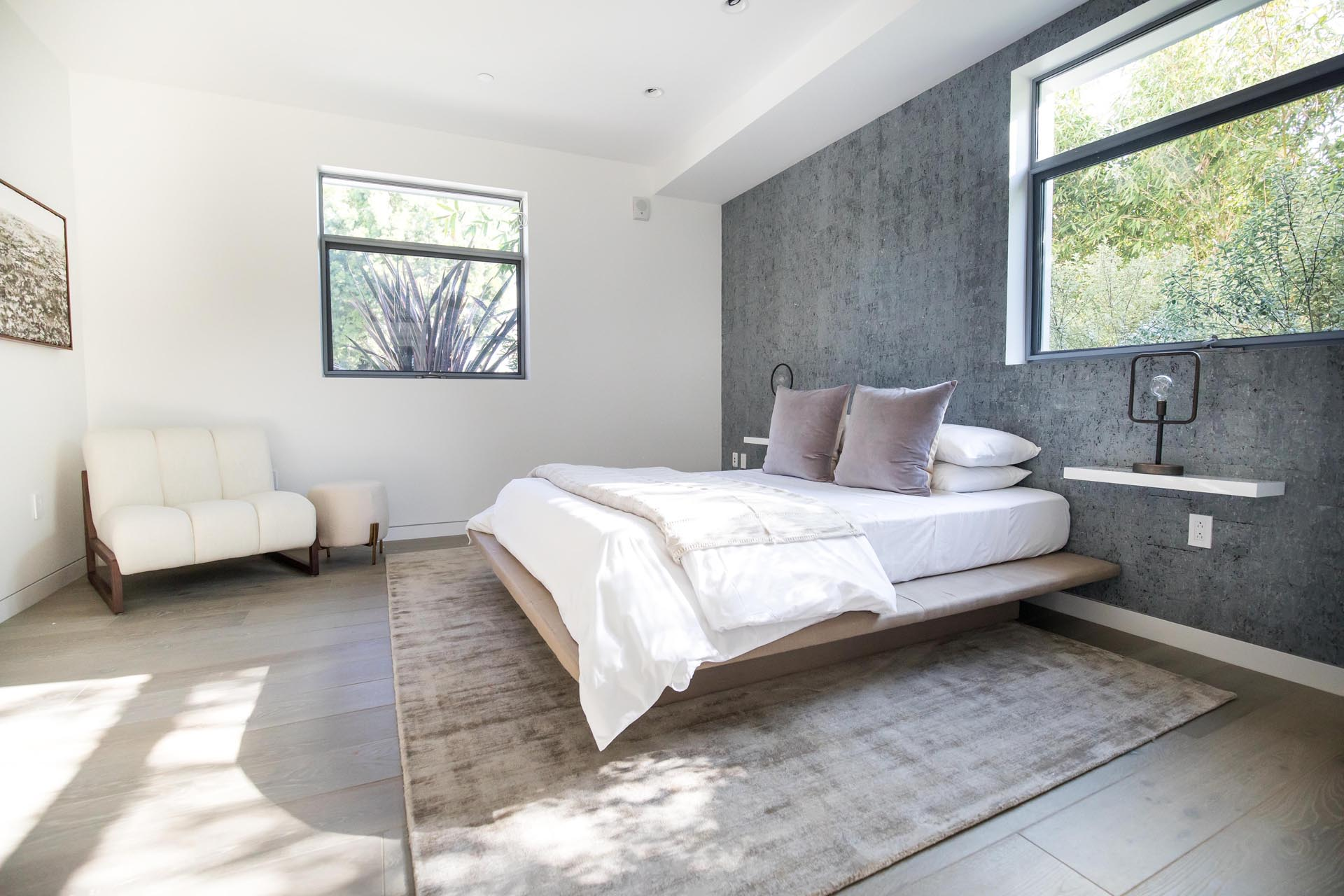 A minimalist bedroom with wall-mounted bedside tables.