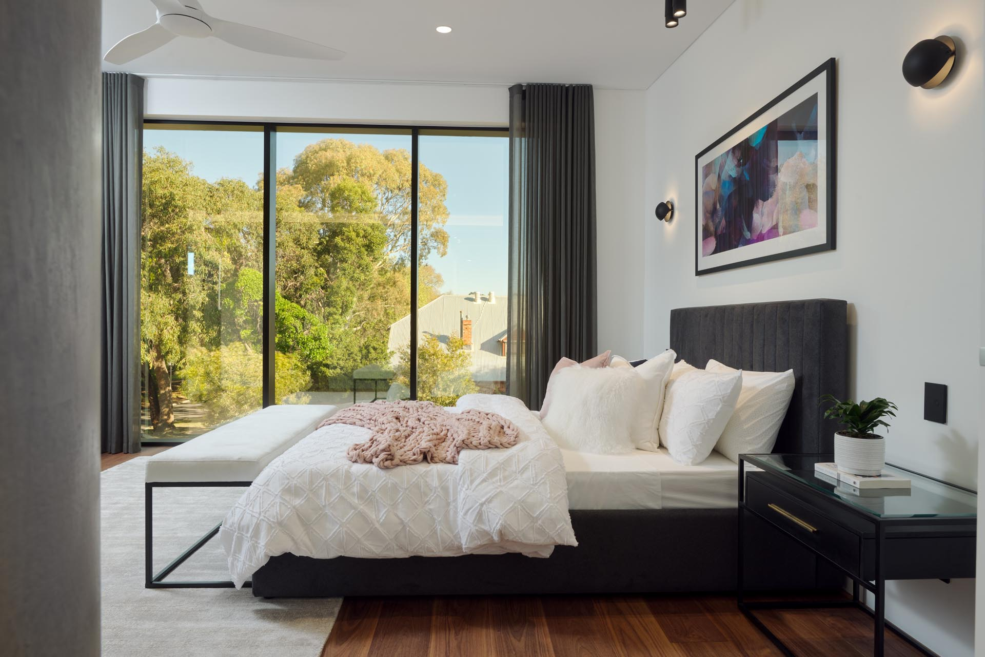 A modern master bedroom with rich wood floors that add a sense of warmth, while an upholstered grey bed frame complements the floor-to-ceiling grey curtains.