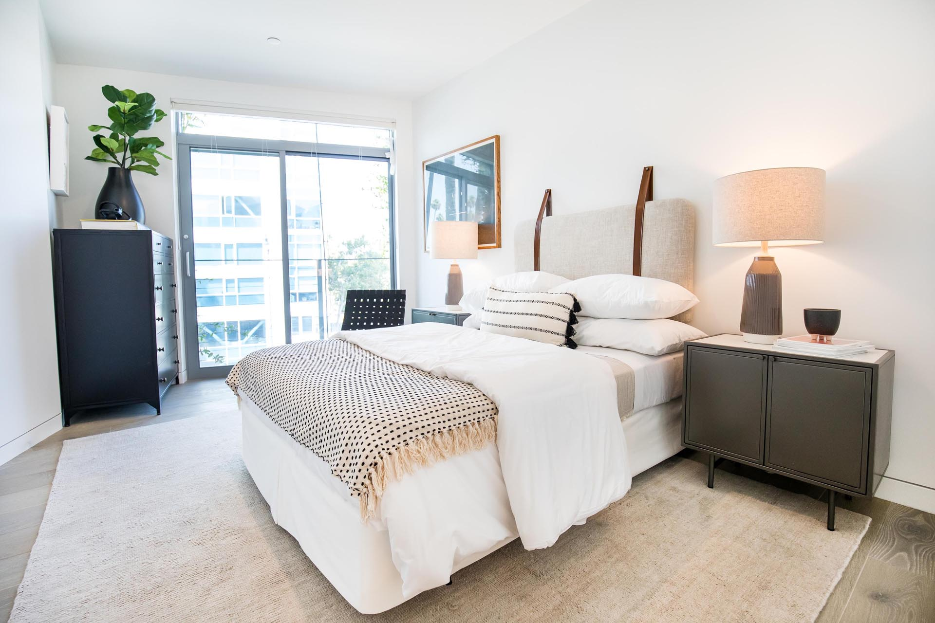 A modern bedroom with a wall mounted headboard.