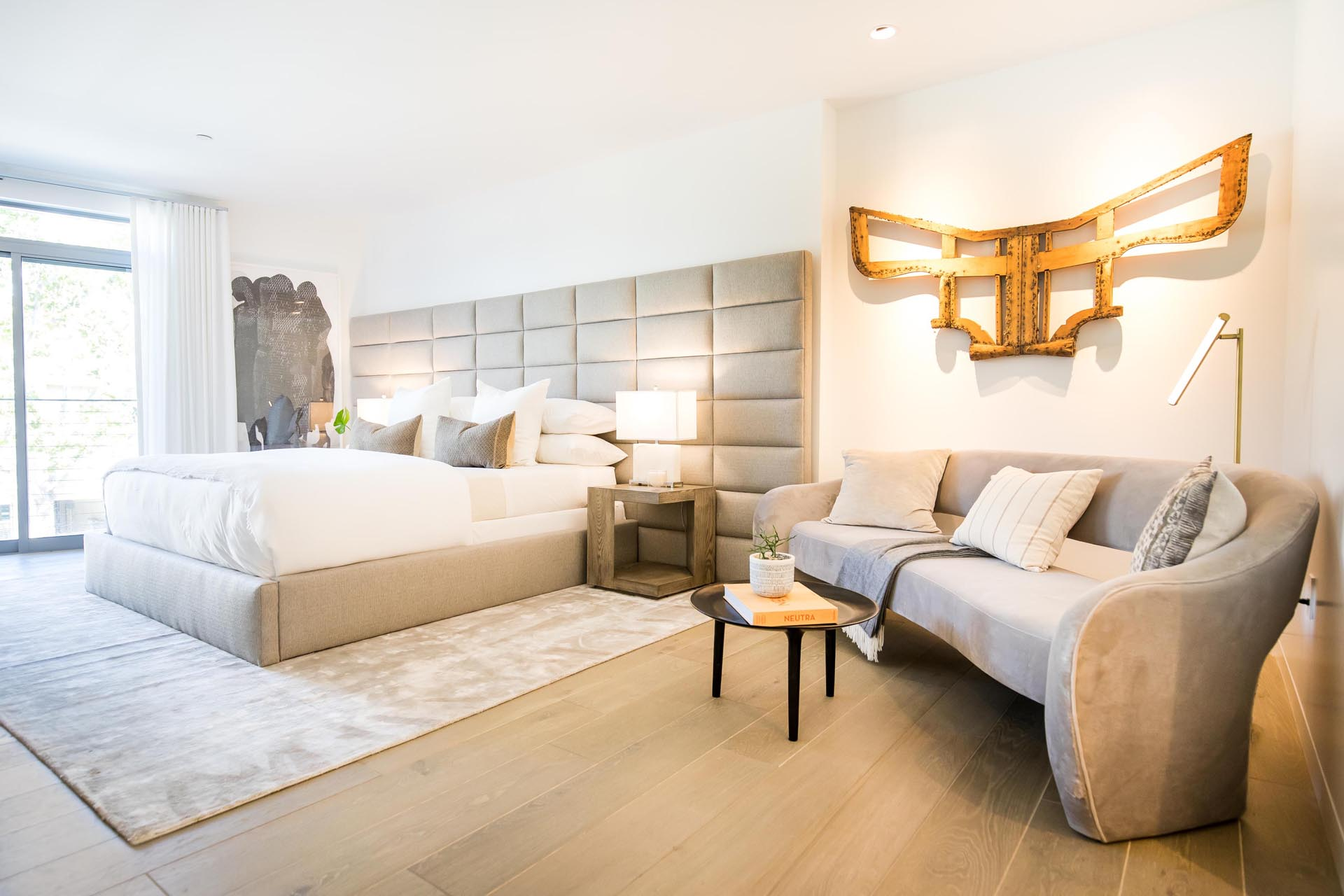 A modern bedroom with an oversized upholstered headboard.