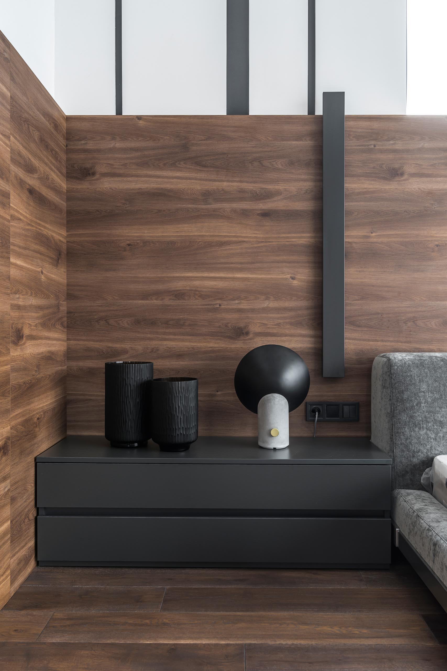 A modern bedroom with wrap around wood accent wall.