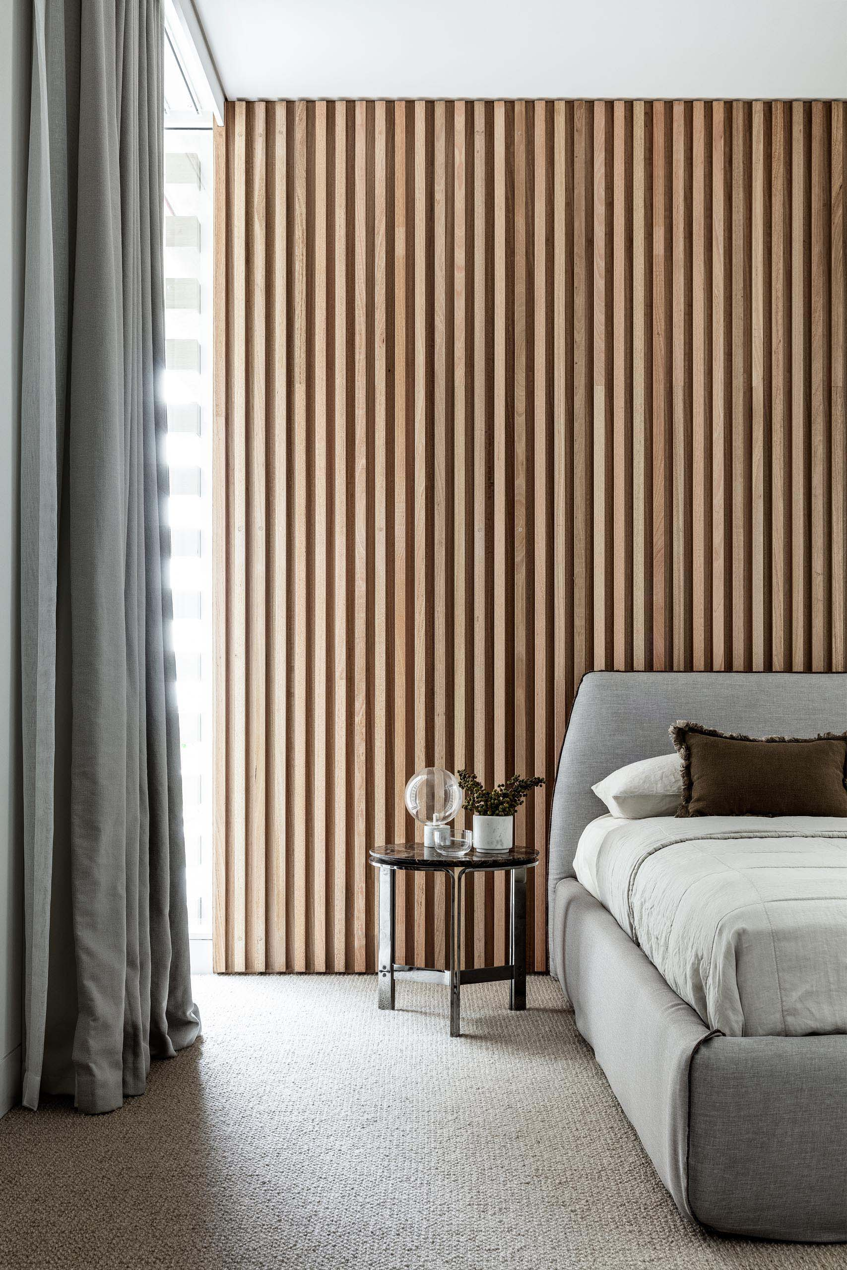 In this modern bedroom, a wood slat wall has been used to create an accent wall behind the grey upholstered bed.