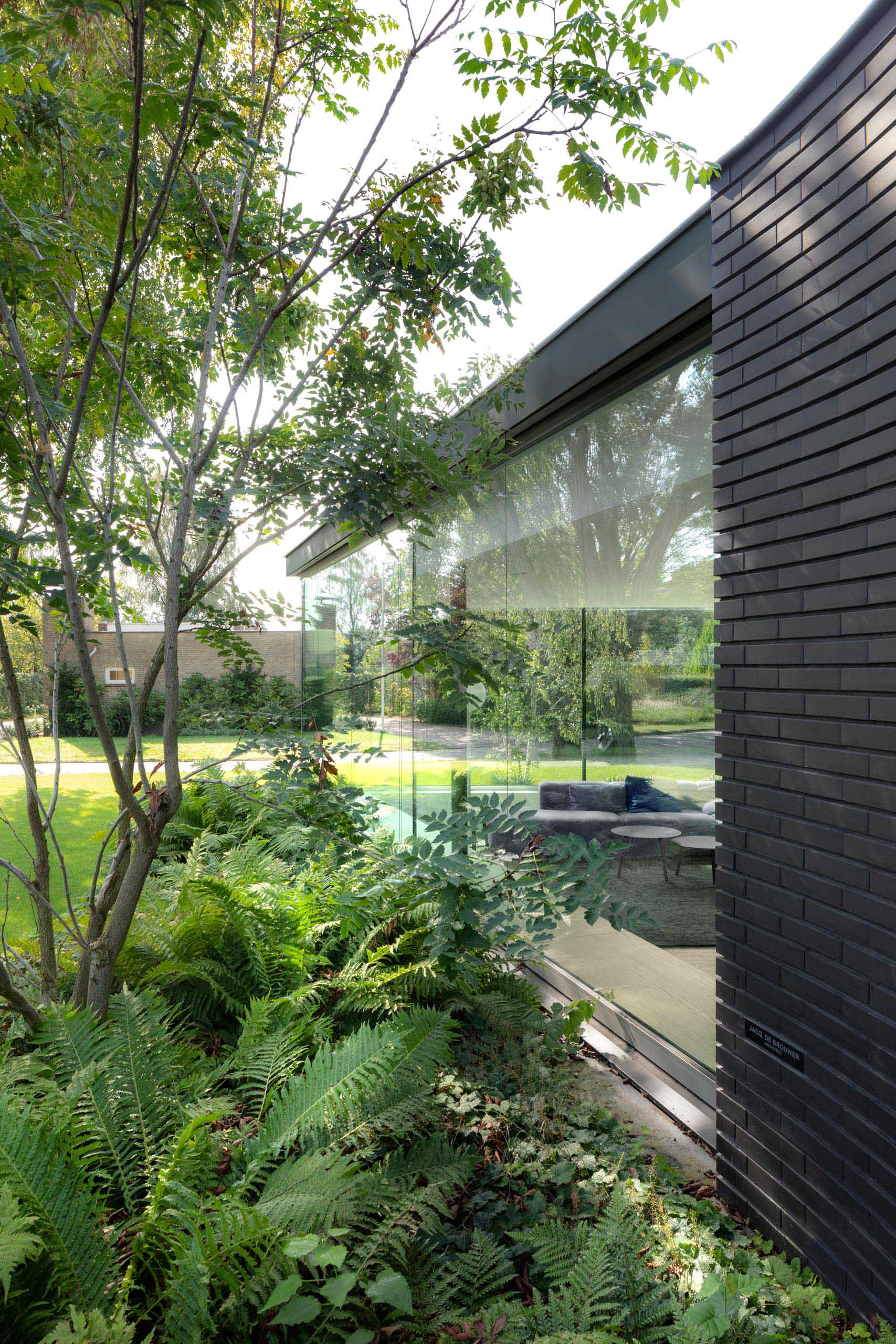 A modern home with a black brick exterior and large glass walls that fill the interior with an abundance of natural light.