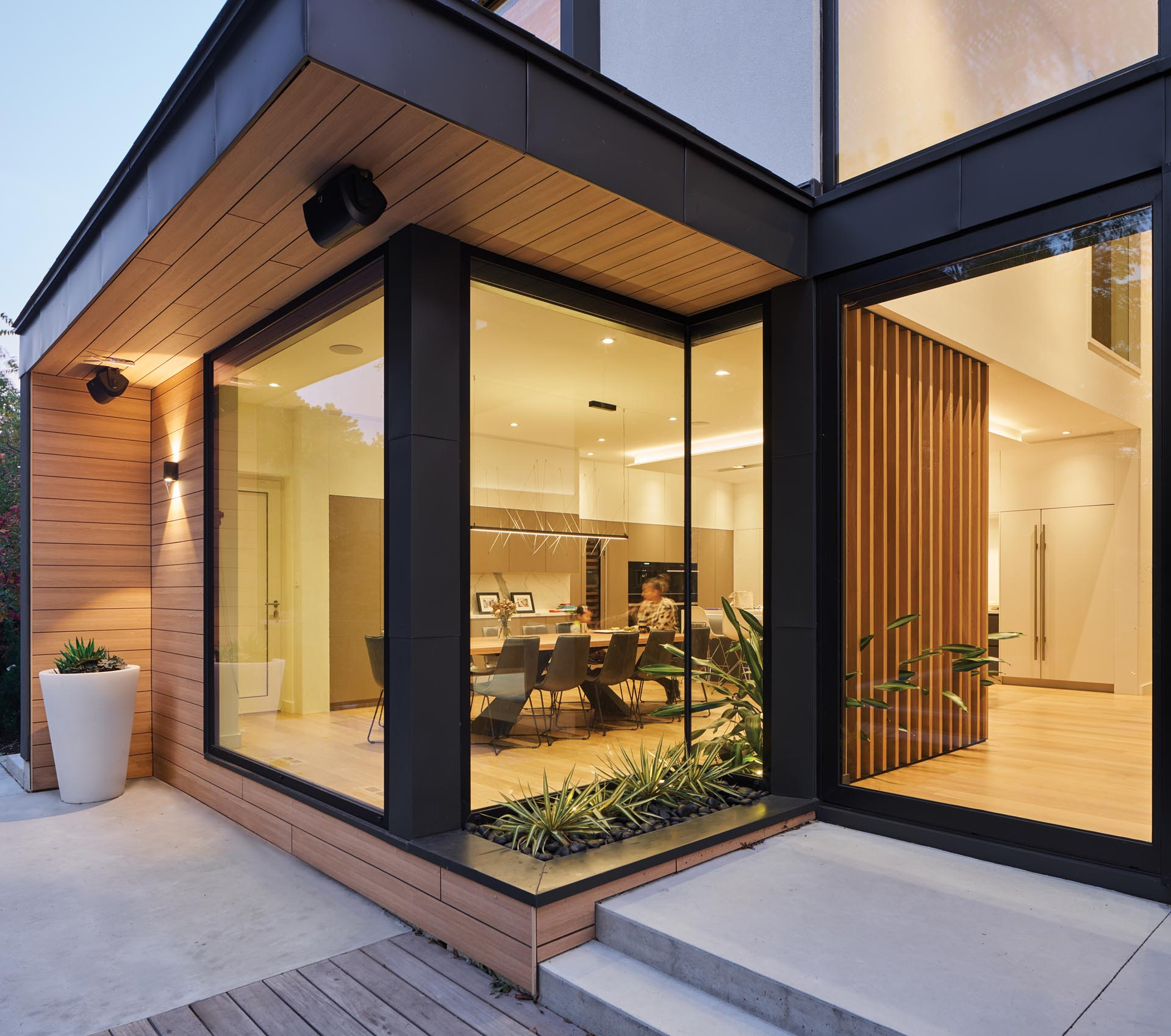 A modern house with a built-in planter, and black-framed windows and sliding glass doors.