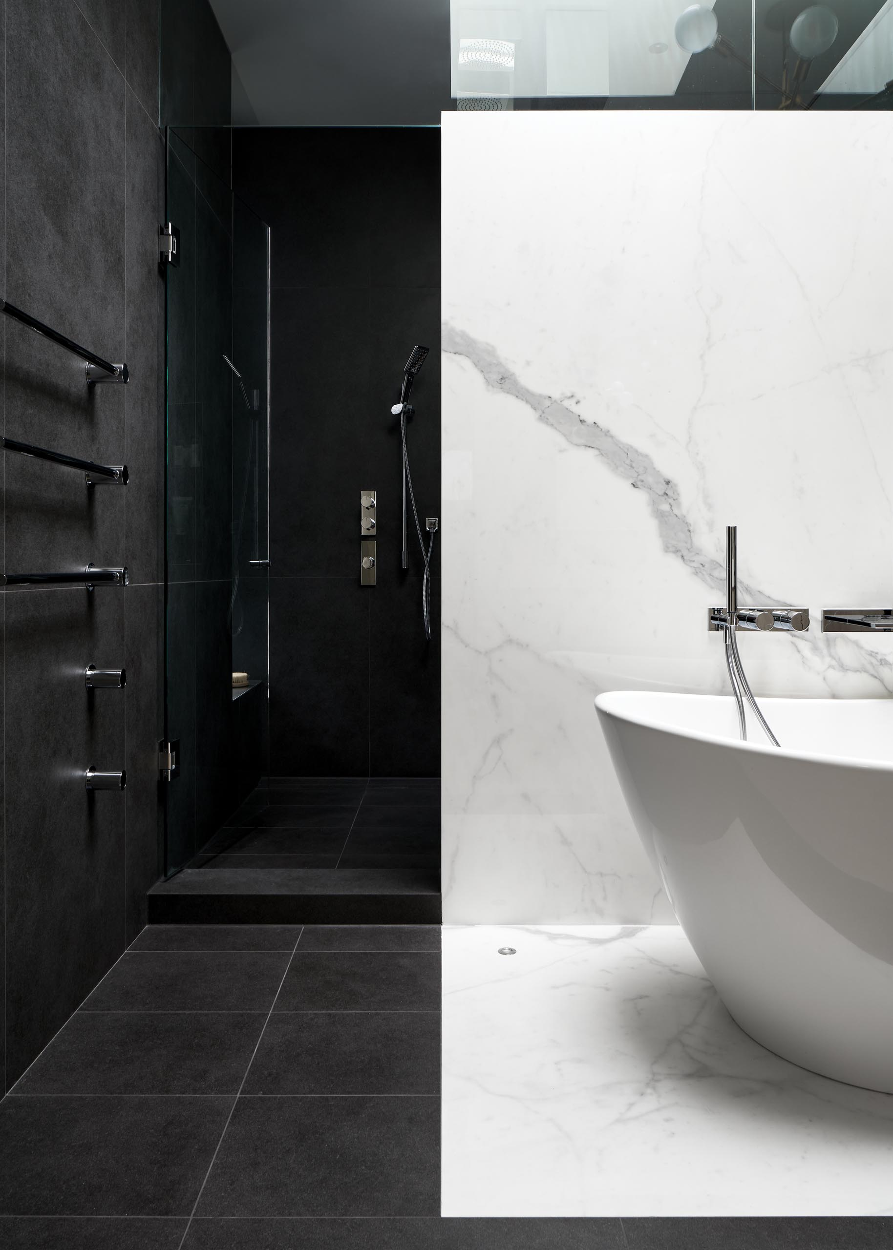 In this modern bathroom, white and black porcelain slabs are combined to create a dramatic contrast.