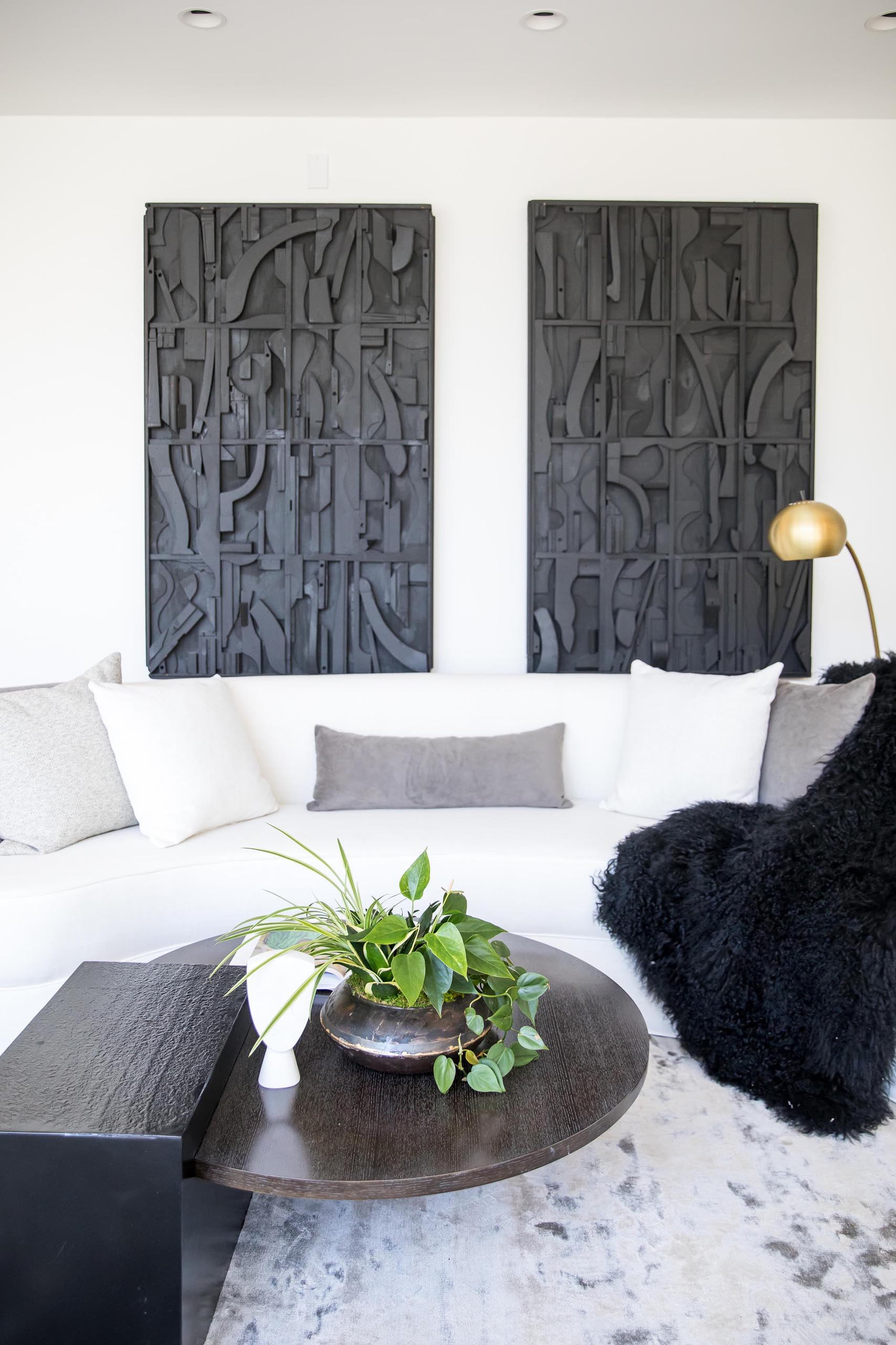 A modern living room with a white sofa and black artwork.