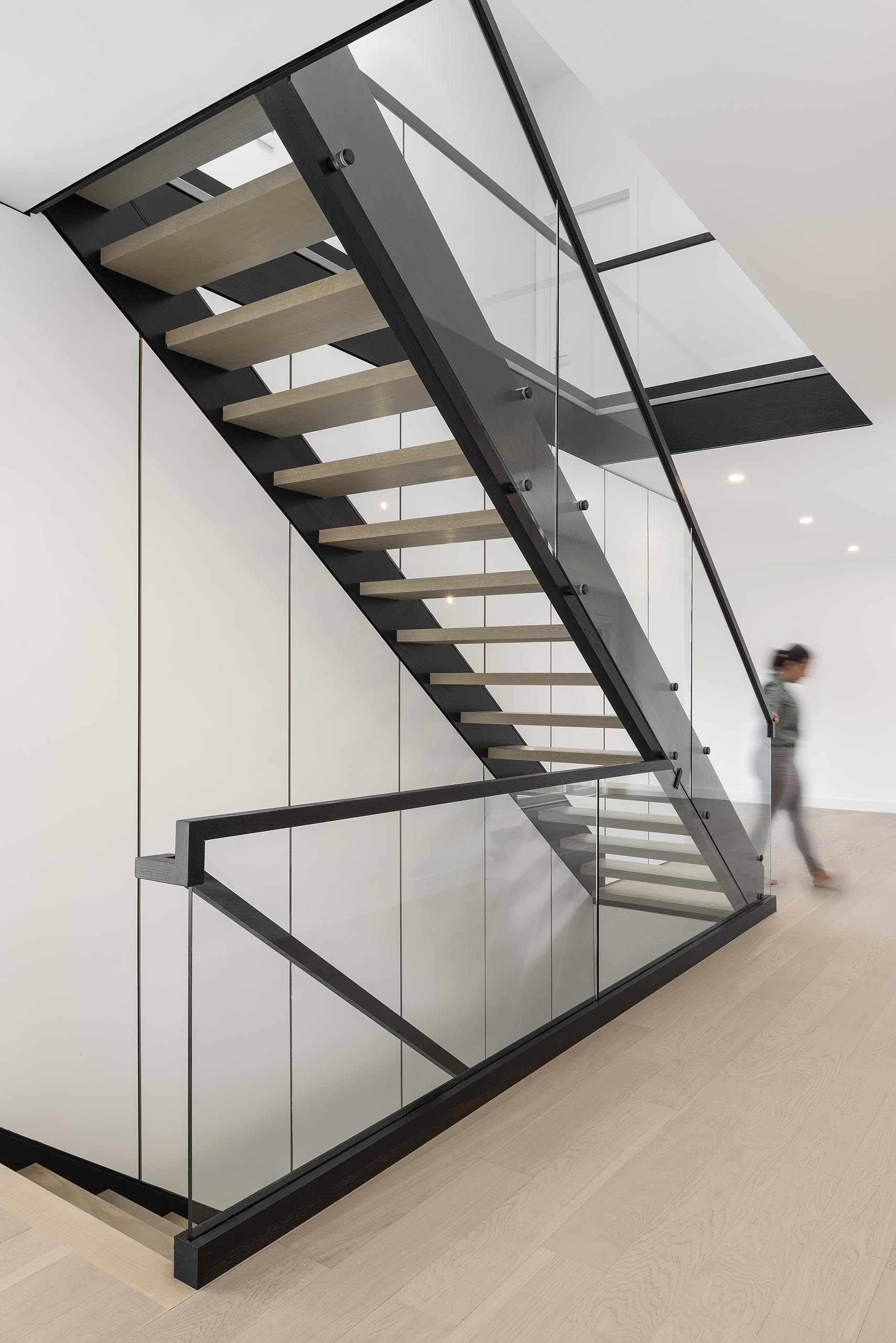 A modern staircase with a black steel support and floating light wood treads.