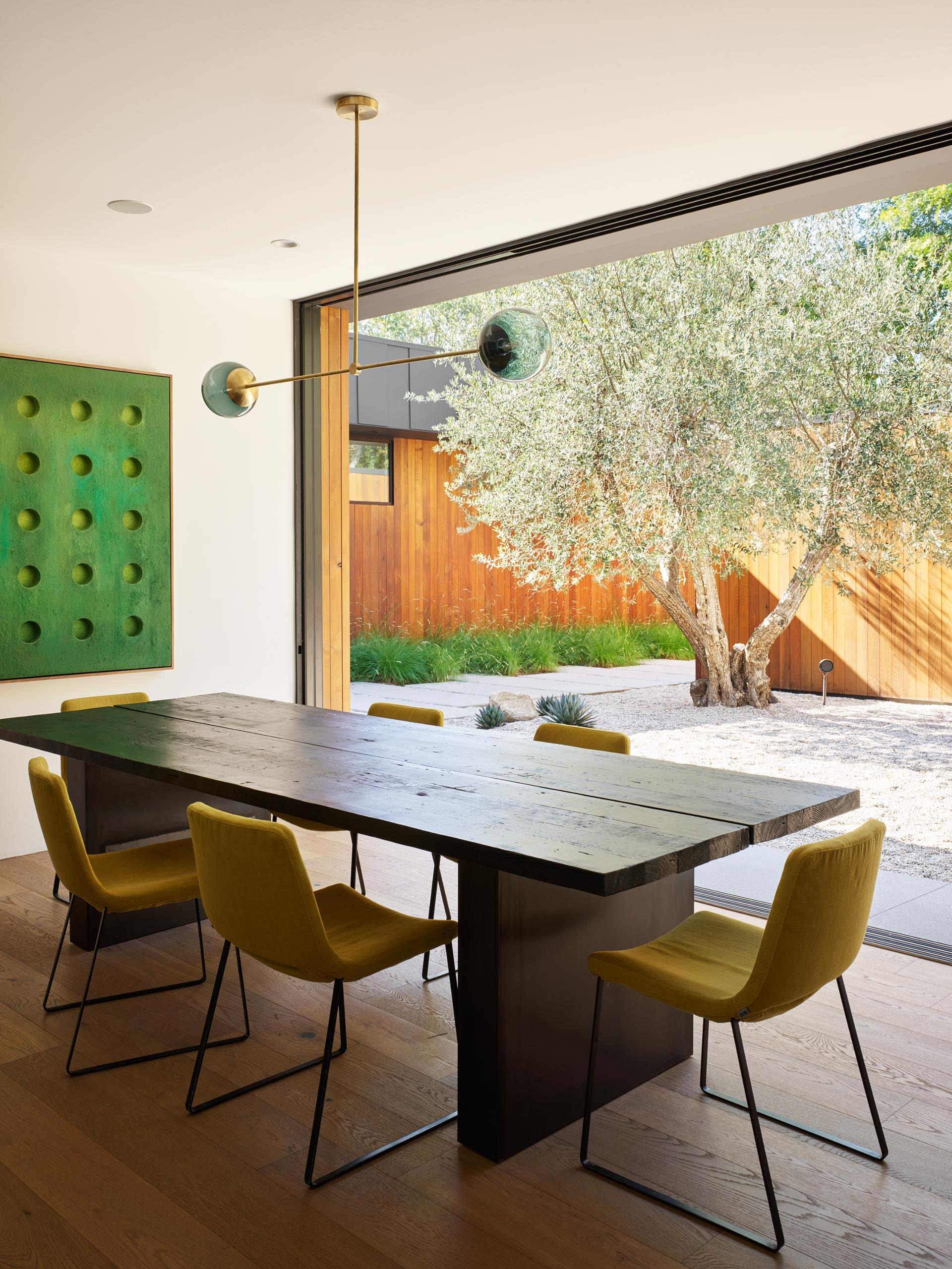 A modern dining room with a wood table, upholstered chairs, and sliding doors that open to a courtyar.