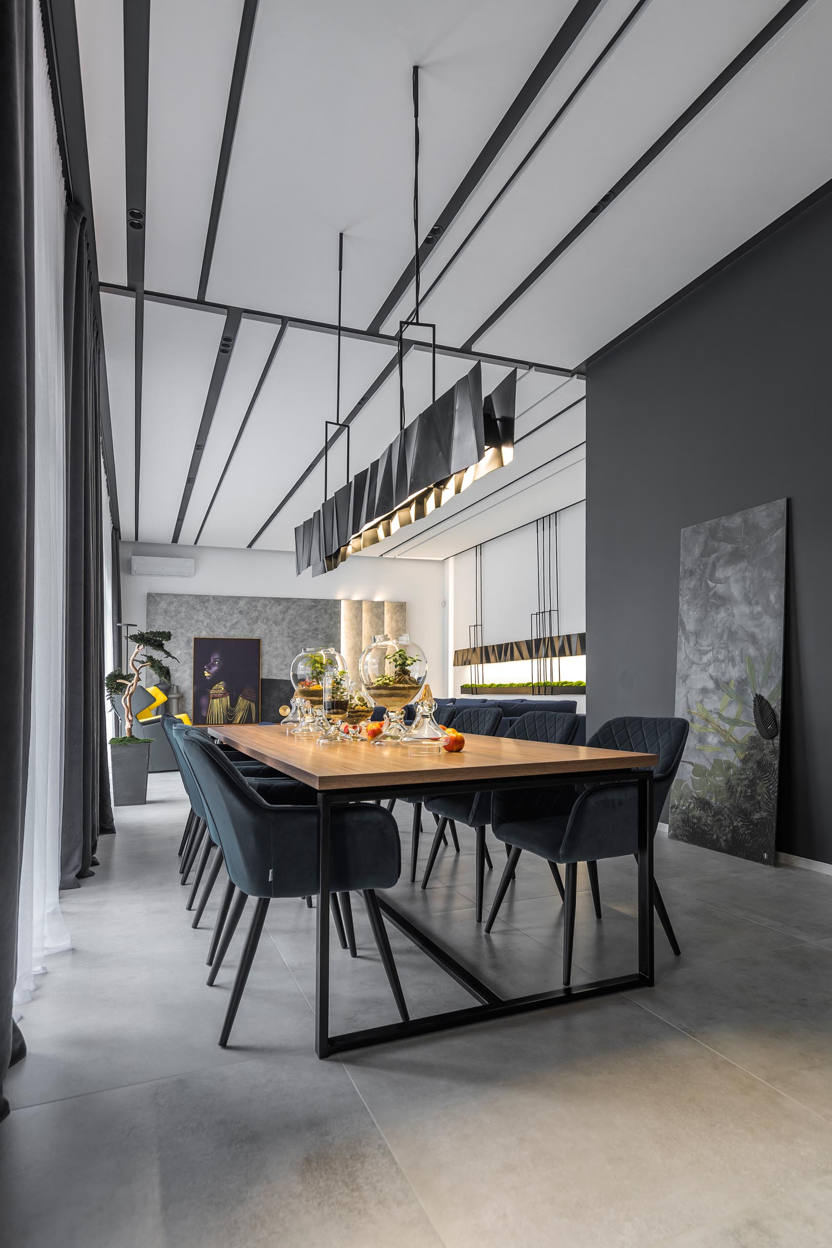 A modern dining room with wood table and a long matte black metal lighting fixture.
