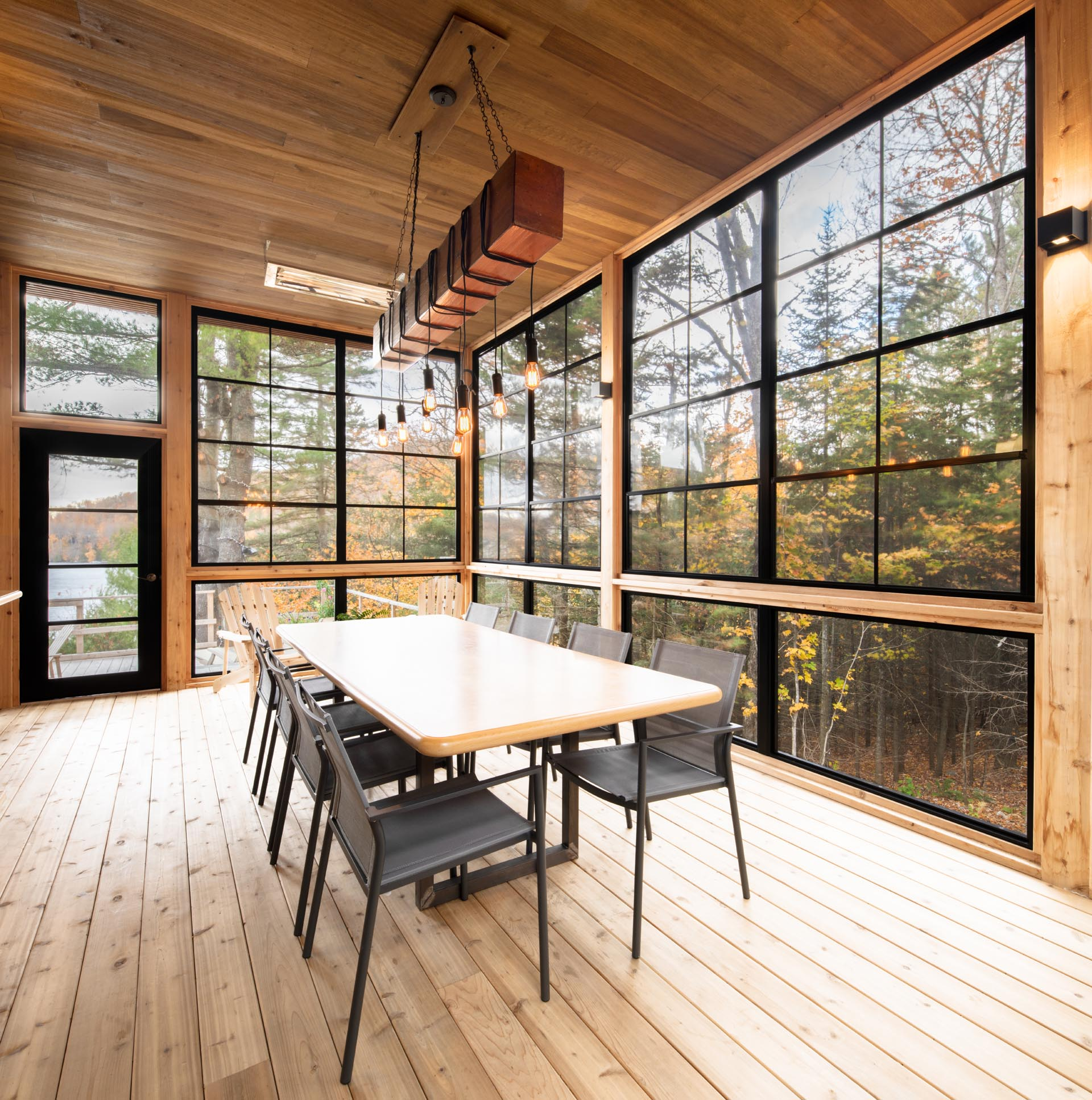 A screened-in porch with black-framed windows is furnished with a large dining table, perfect for group gatherings.