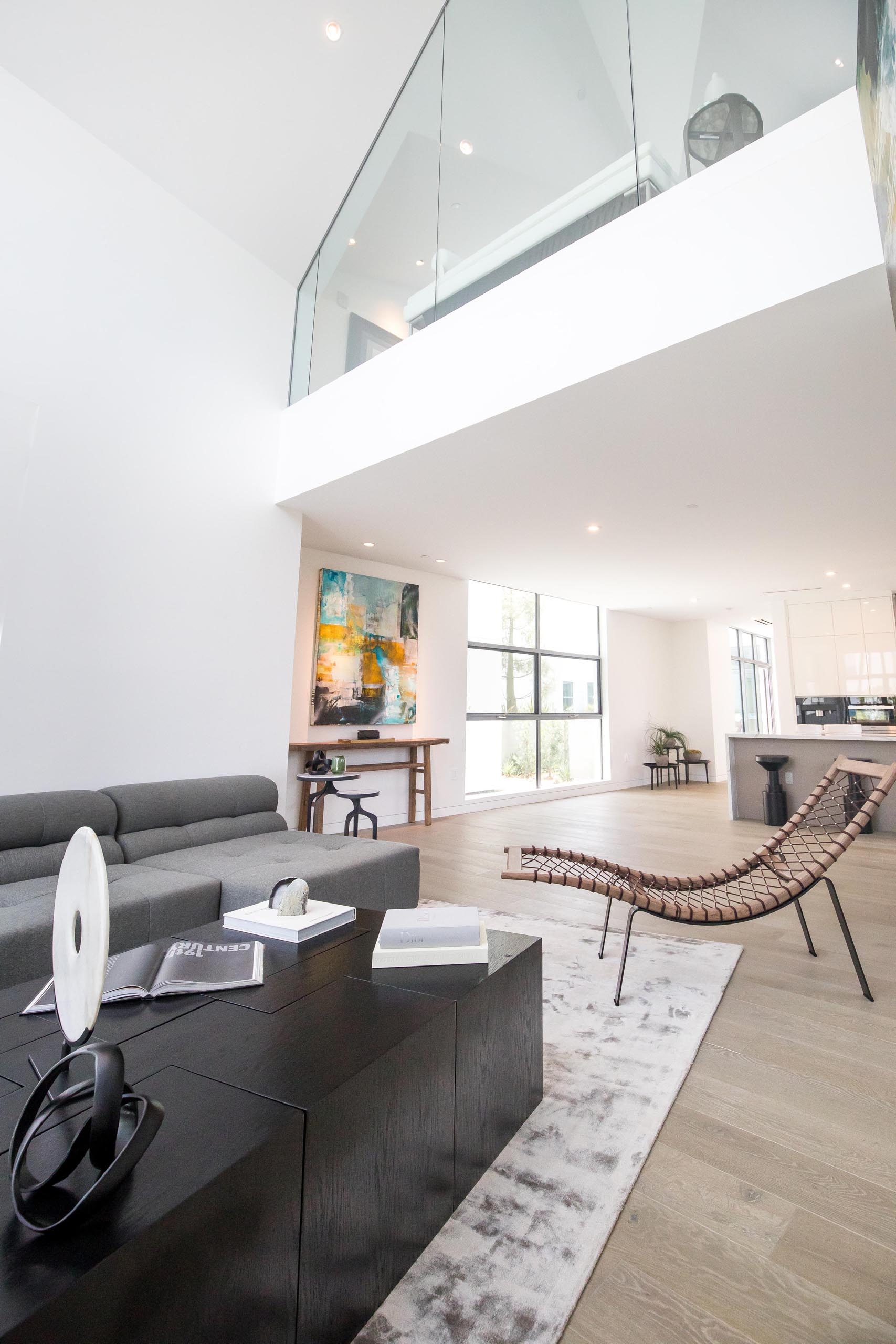 A modern open plan living room with a double height ceiling.