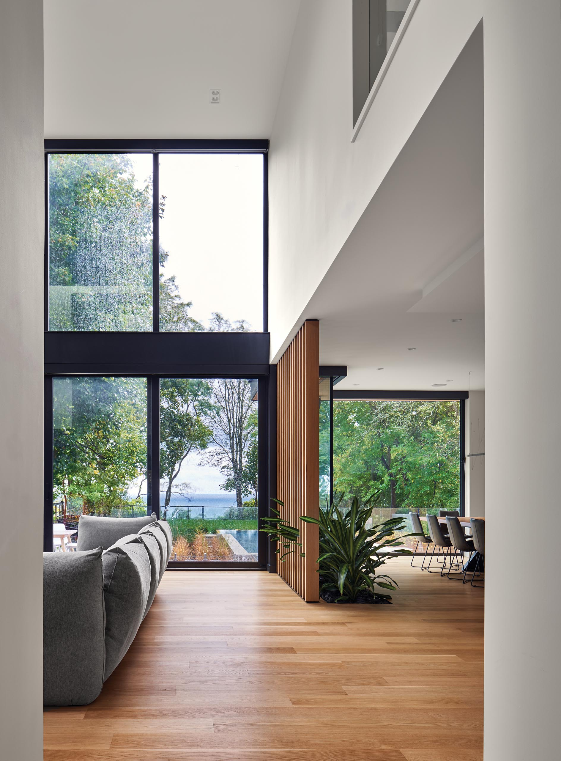 A modern house with double-height windows and ceiling, a wood slat partition, and a built-in planter.