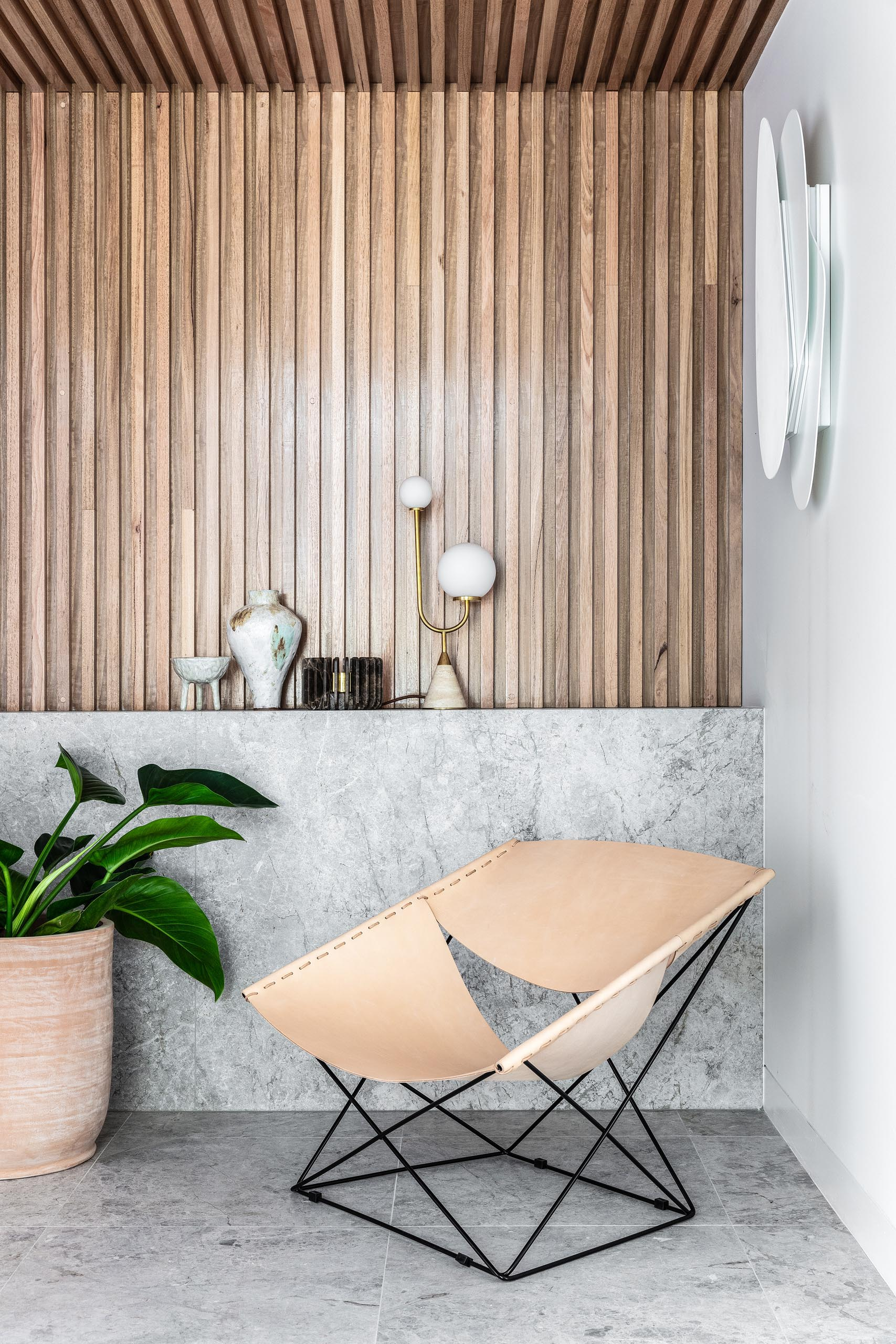 A modern entryway with a leather chair, a wood slat wall that flows onto the ceiling, and a stone accent that acts as a shelf.