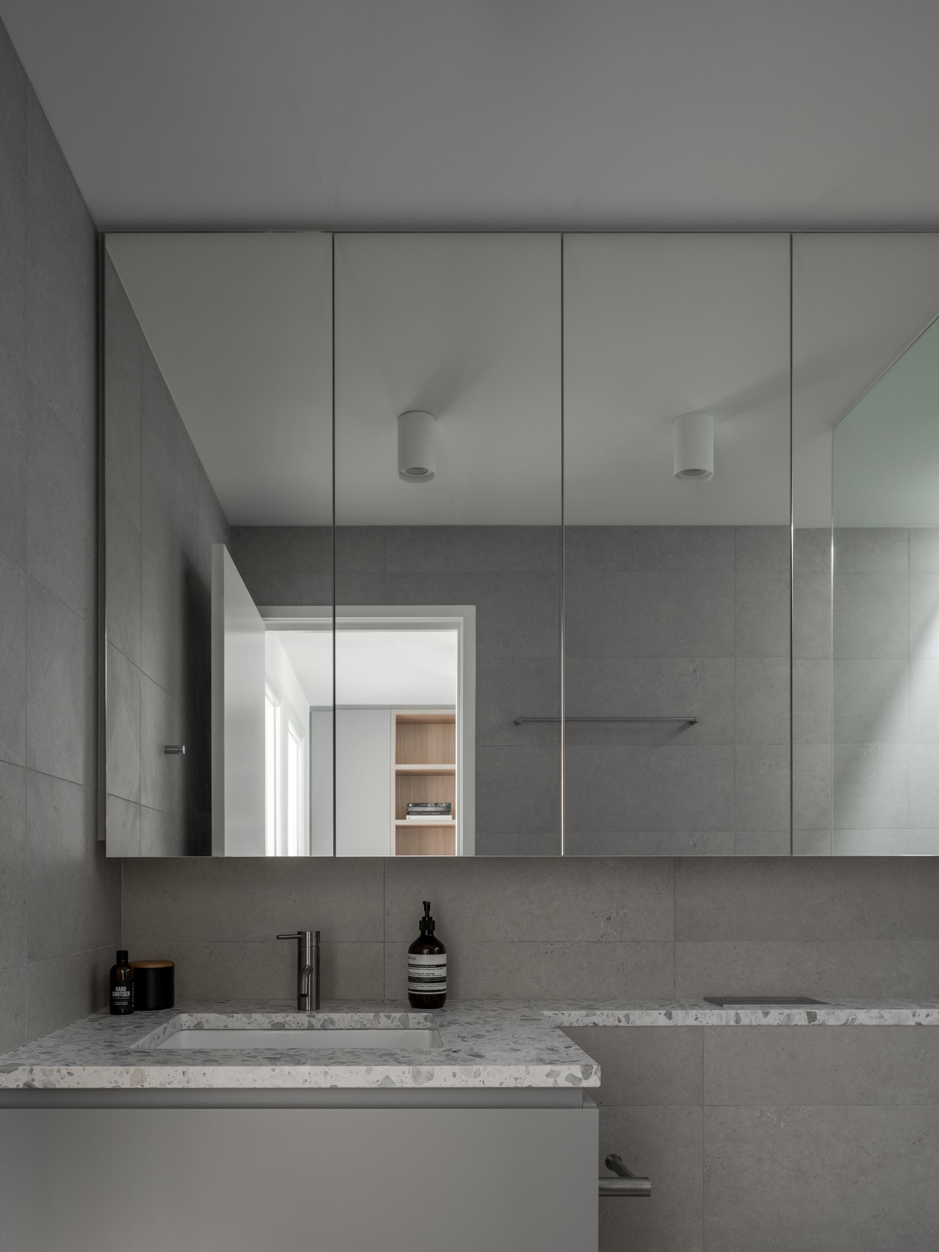 A gray bathroom with a white stone countertop.