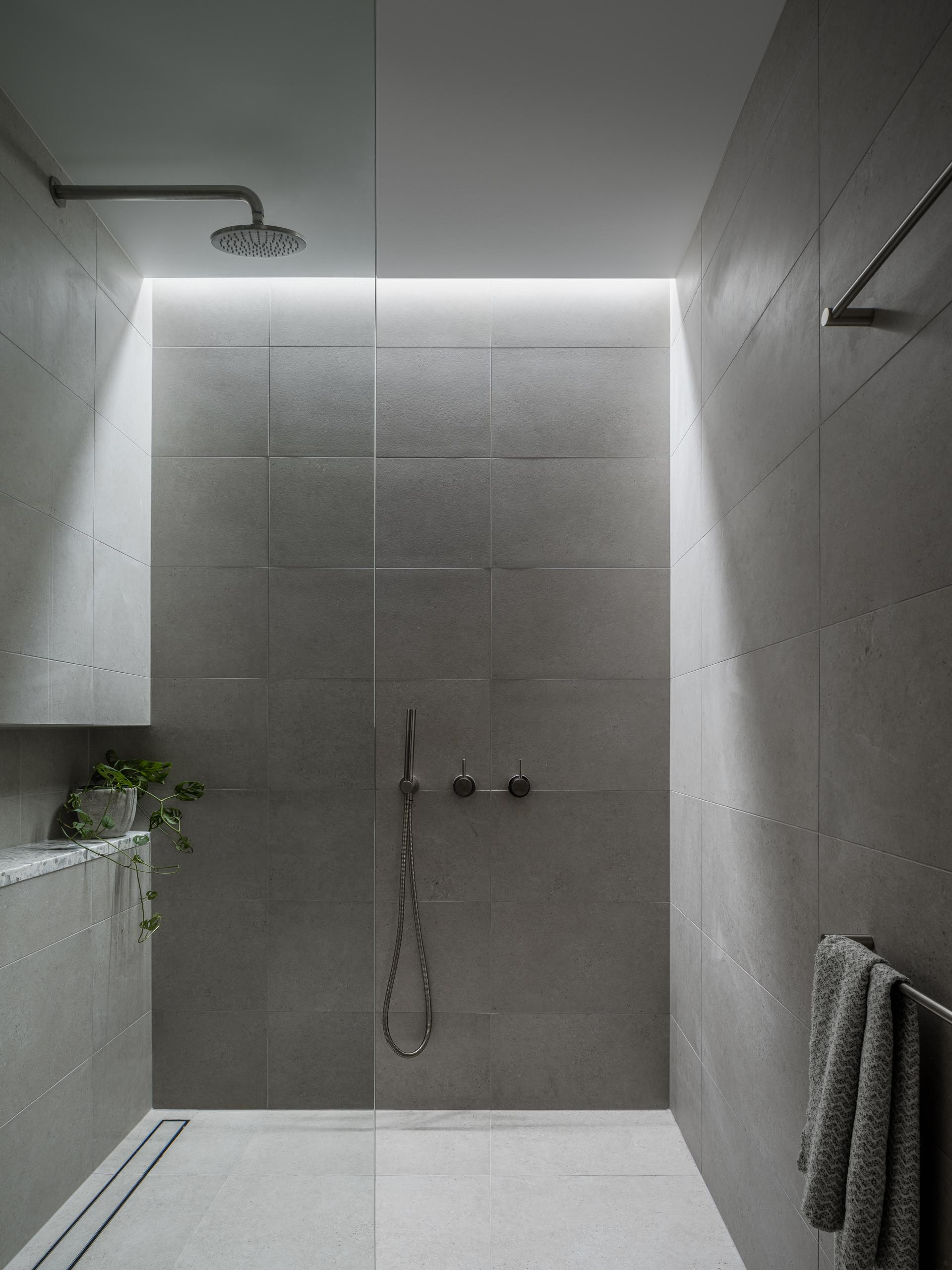 A gray tiled shower with a skylight, shower niche, and a linear drain.