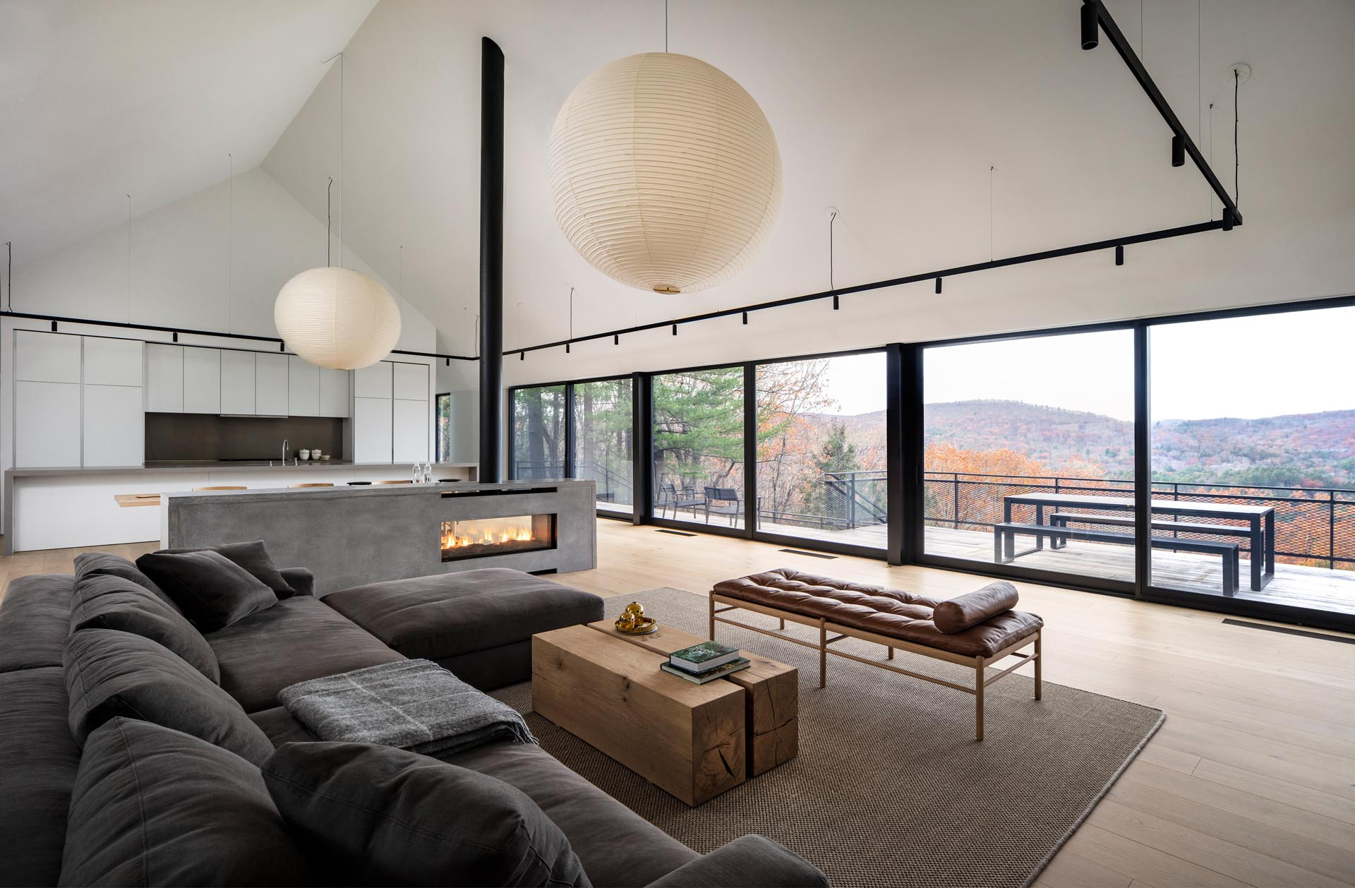 A modern house interior with a great room that includes the living room, a concrete fireplace, the dining room, and a white kitchen.