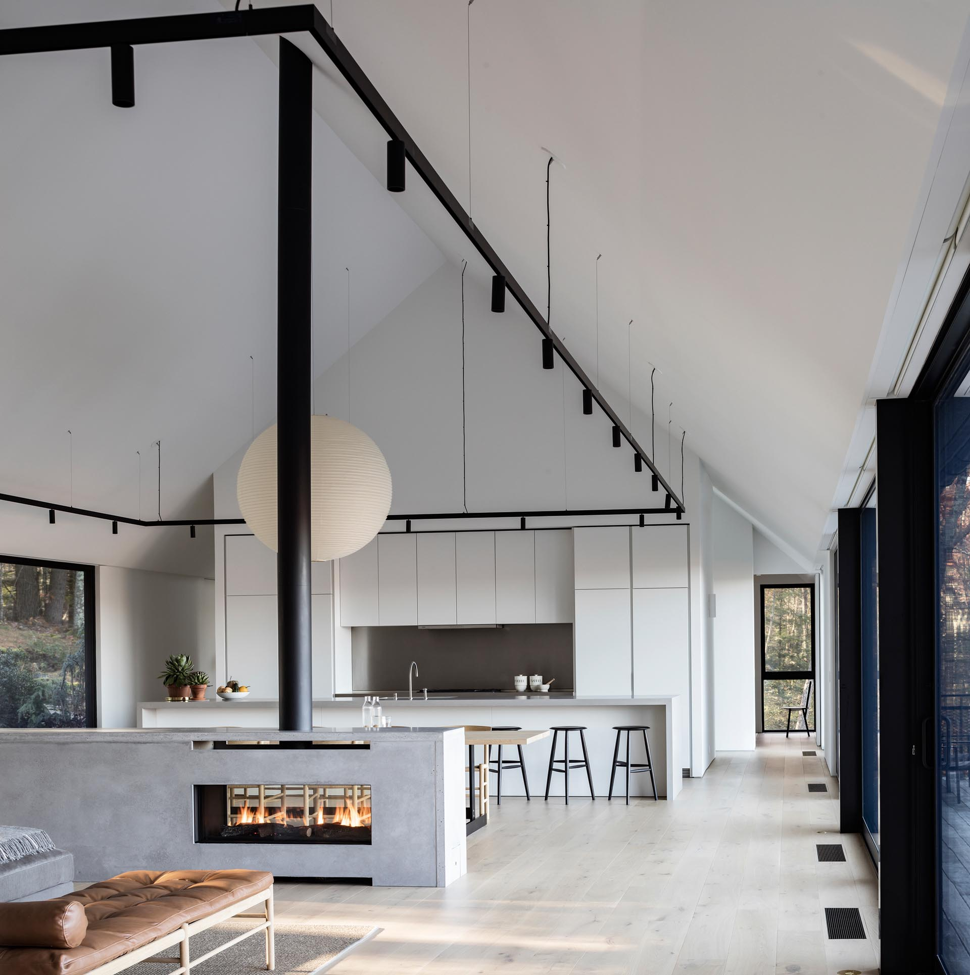 A modern house interior with a see-through fireplace, a minimalist white kitchen, and black accents.
