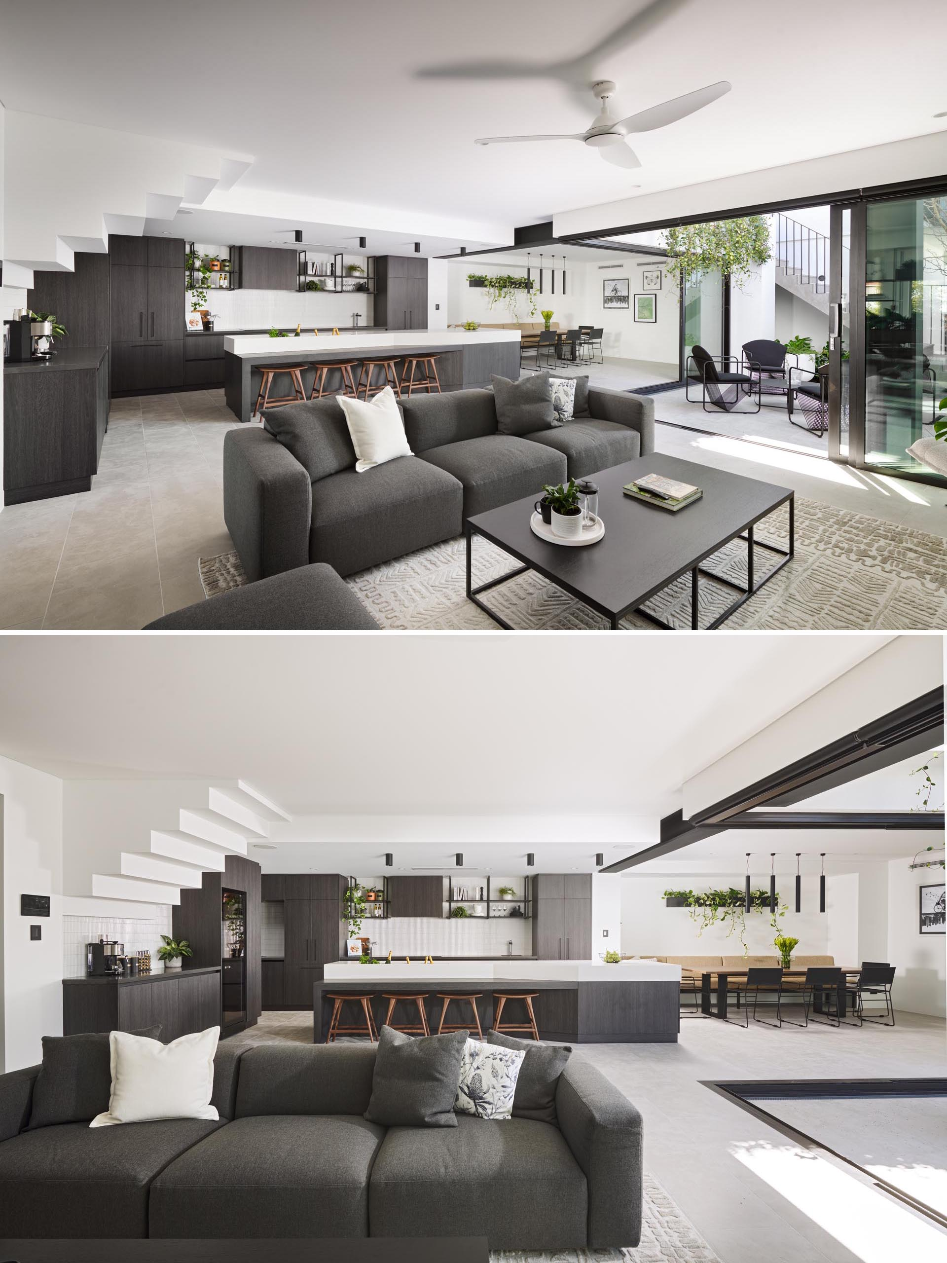 The main social areas of this modern have a color palette that includes grey tones that complement light walls and floors, and black accents.