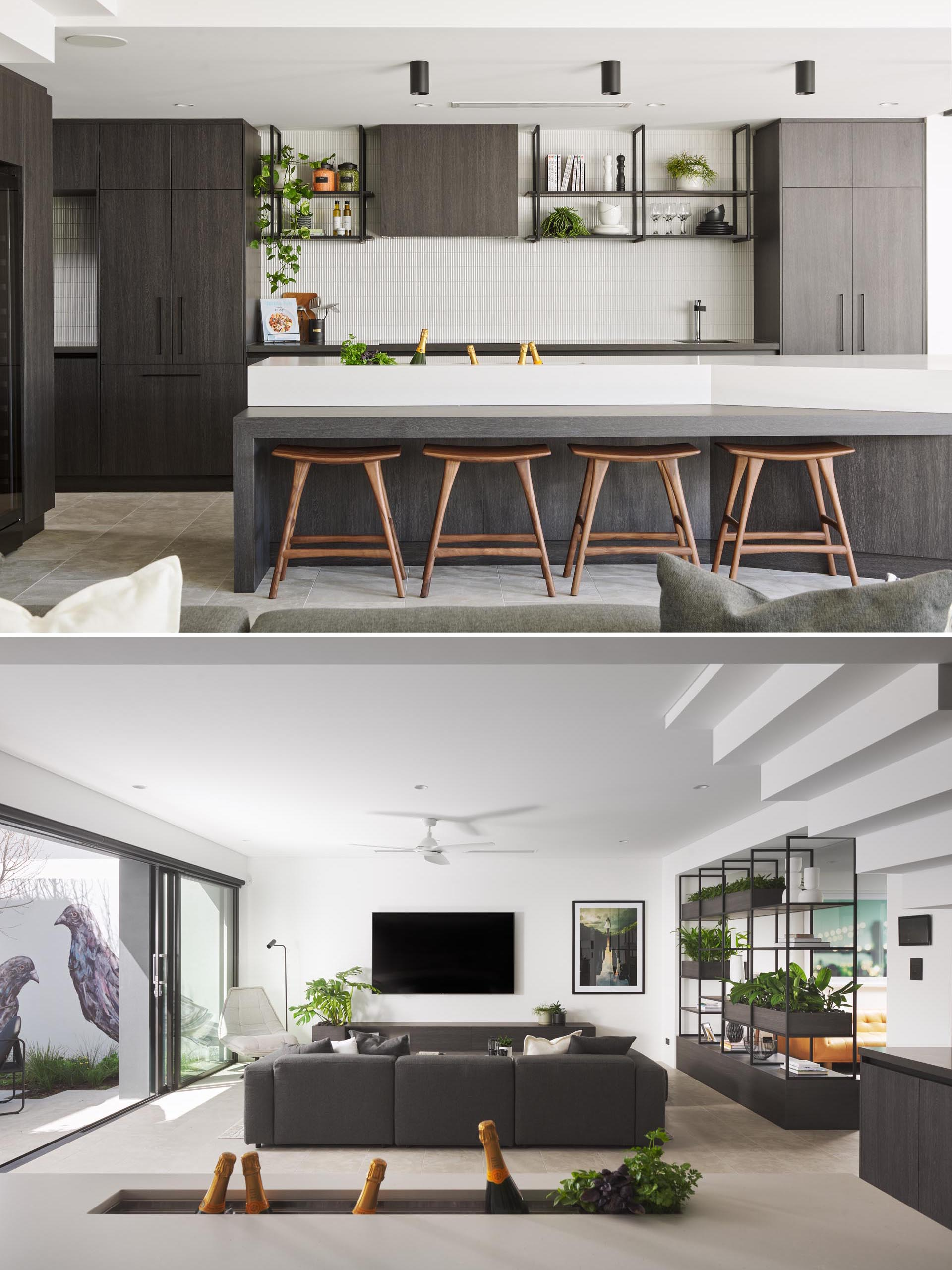 In this mdoern kitchen, dark cabinets and shelves contrast the white tile backsplash and thick white countertop of the island. There's also a drink trough built into the island, ideal for holding wine, champagne, or beer.
