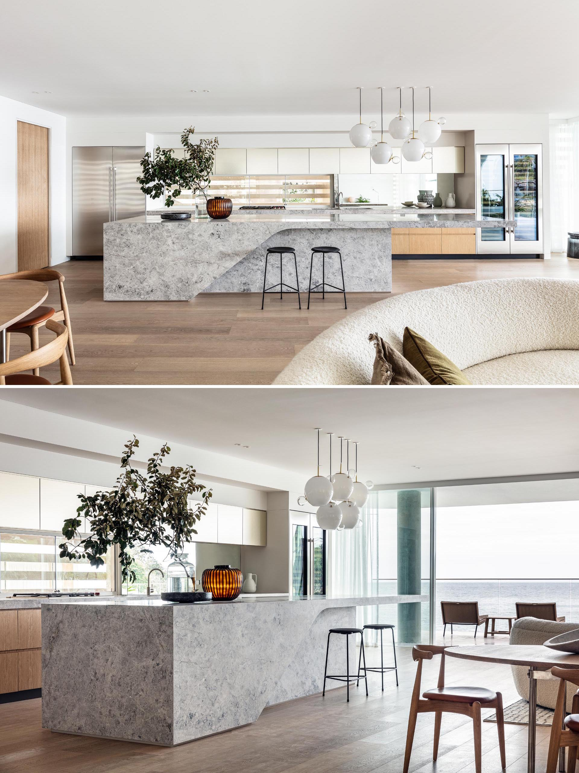 This modern house has a large natural stone kitchen island with pendant lights that hang above the end of the island that's cantilevered.