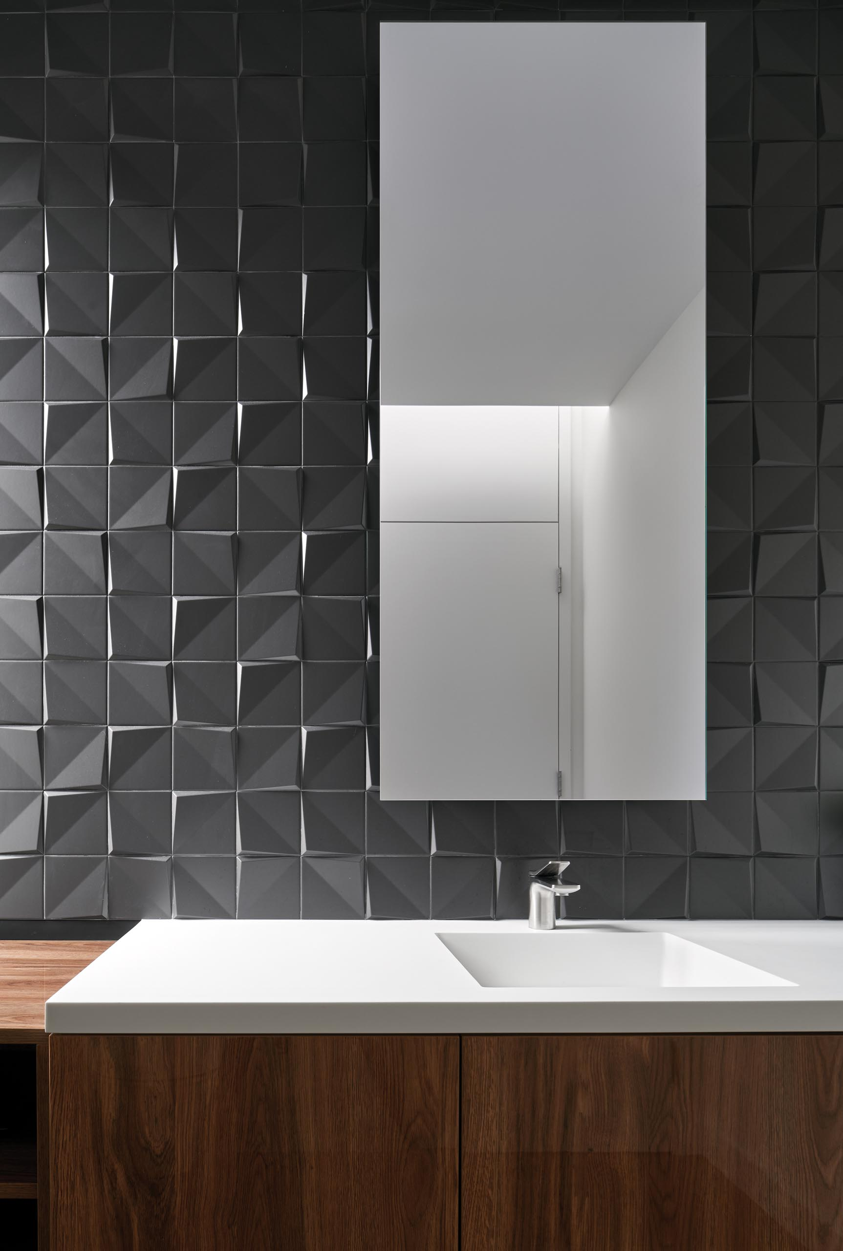 A modern grey and wood bathroom with 3-dimensional tiles that add texture to the wall.