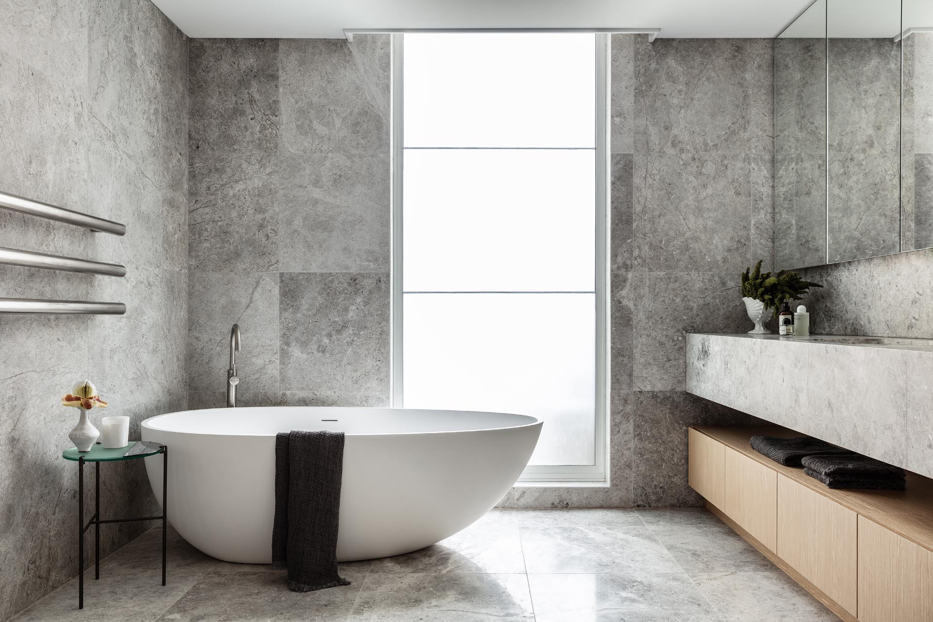 In this modern master bathroom, natural stone with a grey finish covers the walls and floors, as well as the vanity. A floor-to-ceiling frosted window allows the light to pass through, but still allows for privacy.
