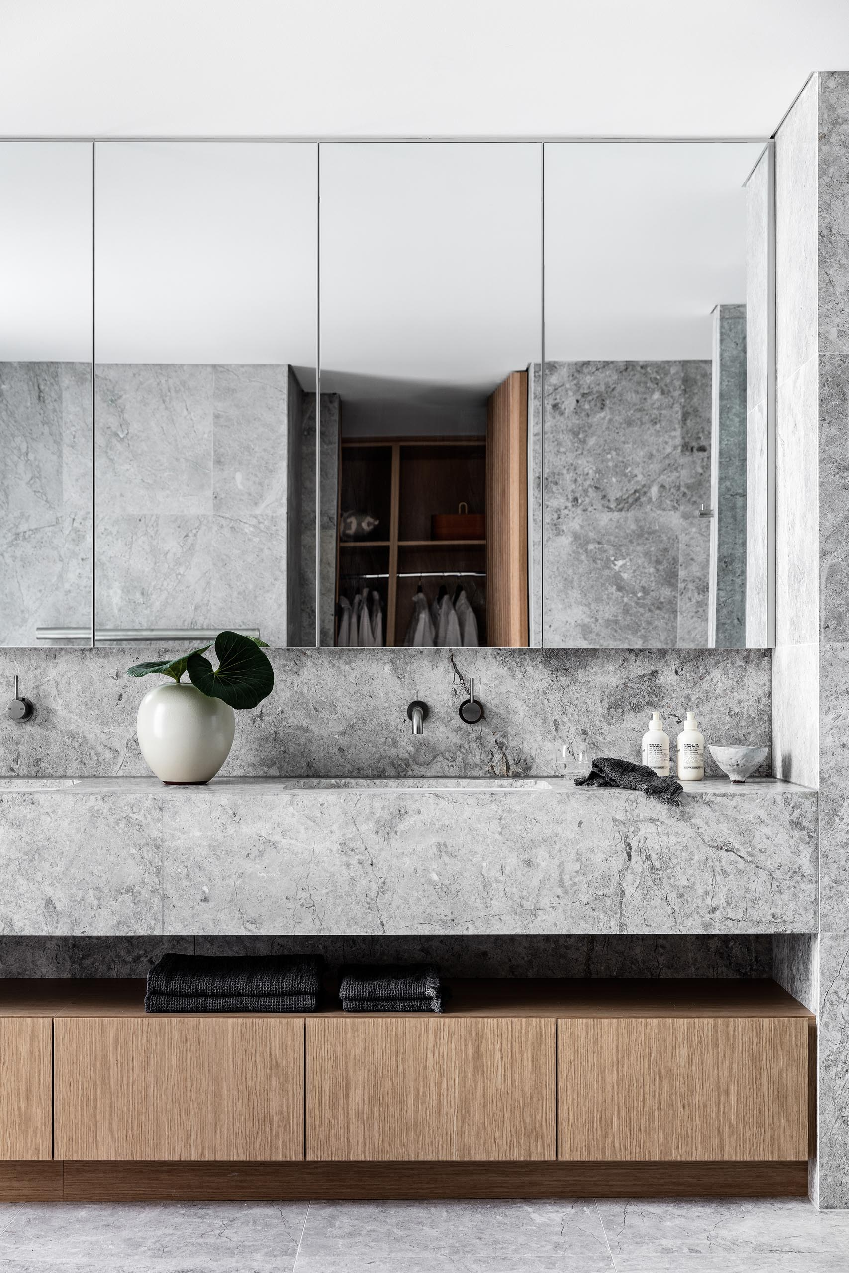 In this modern master bathroom, natural stone with a grey finish covers the walls and floors, as well as the vanity.
