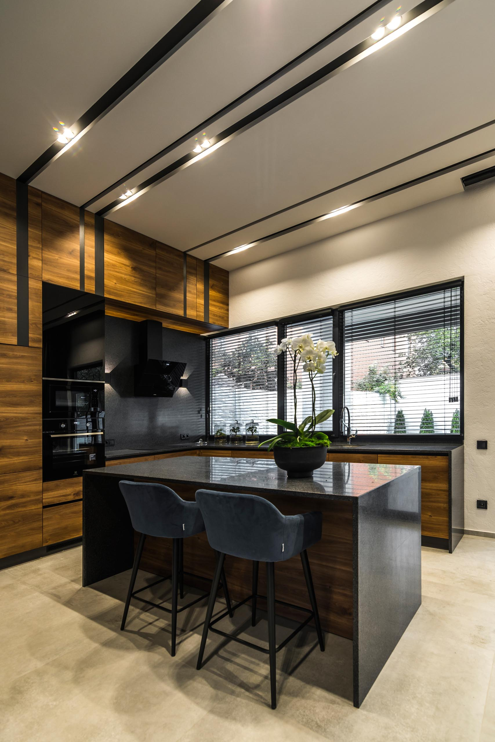 A modern gray, black, and wood kitchen with island.
