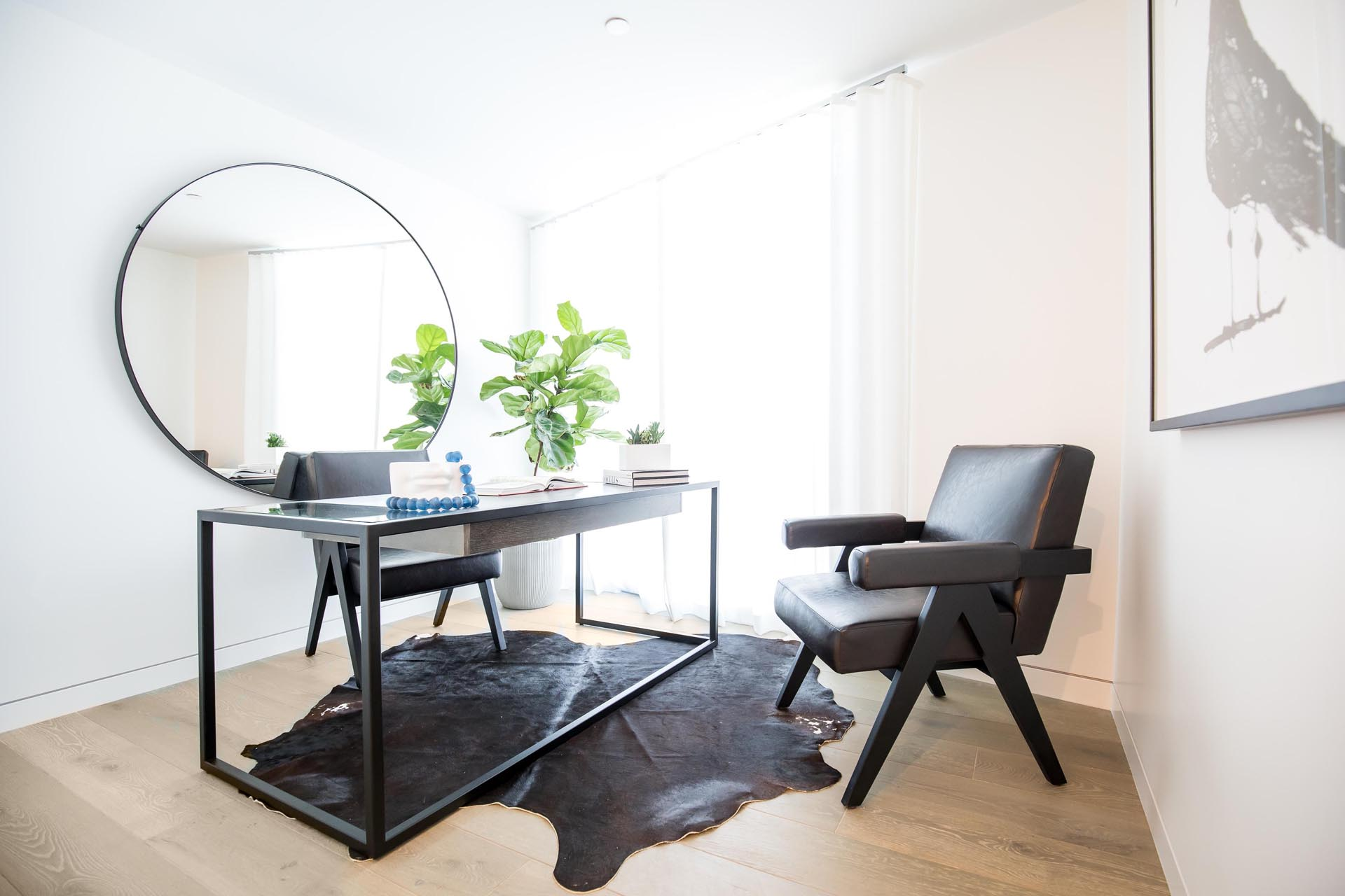 A modern home office with a large round mirror to reflect the light.