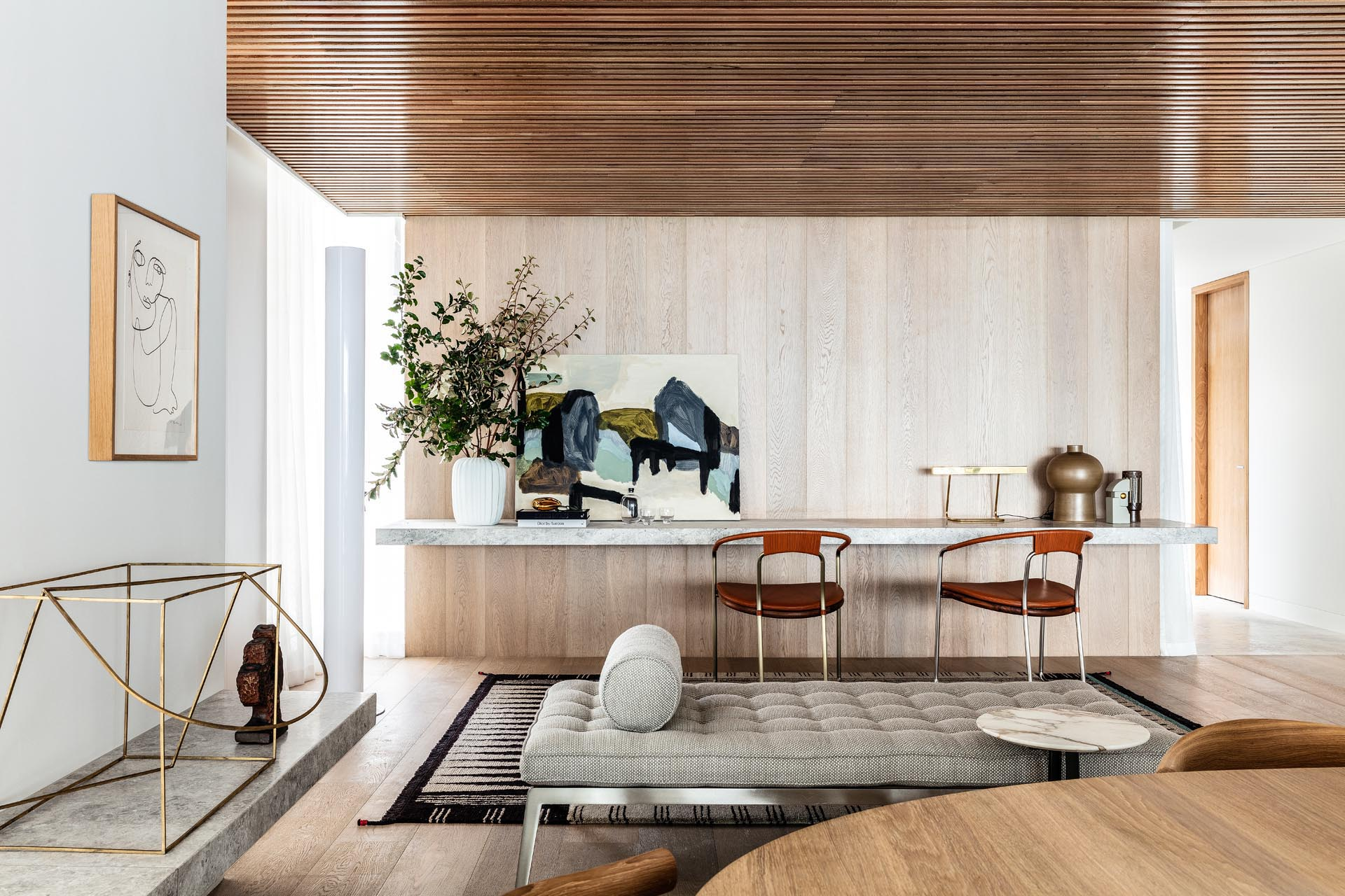 A floating stone desk lines the wall, while wood slats cover the ceiling.