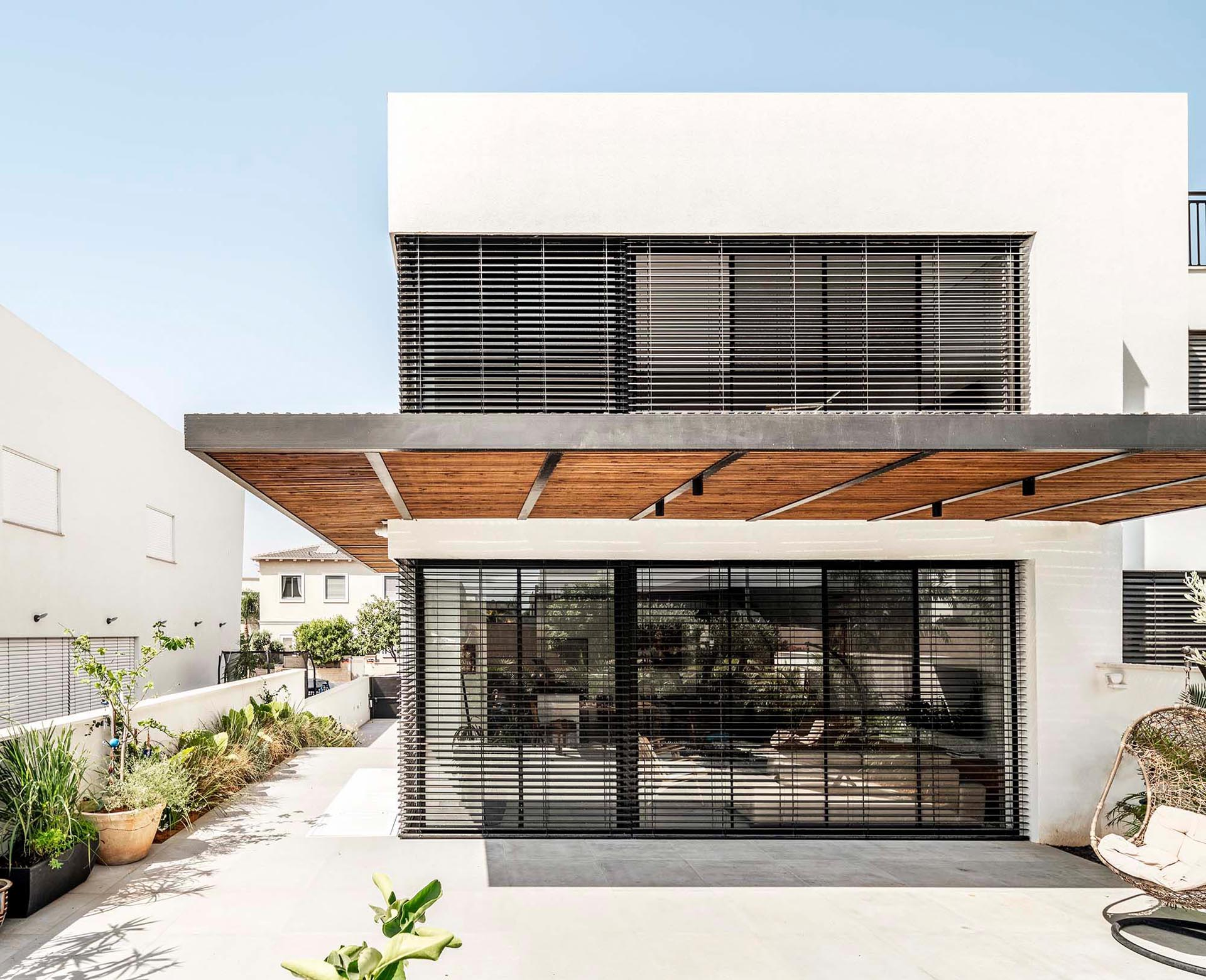 A modern home with a white facade, black window frames, and wood accents.