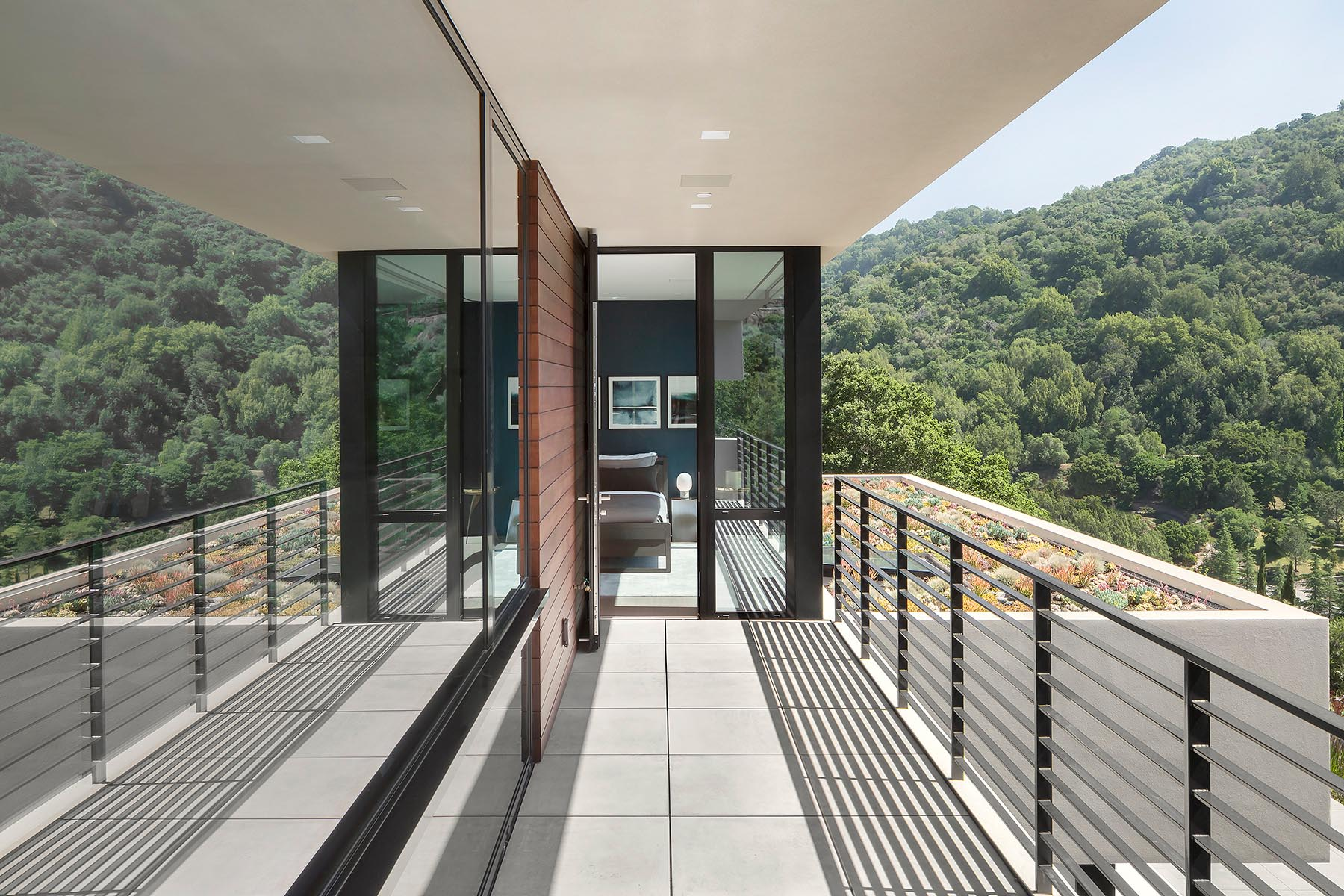 A bedroom opens up to a balcony with views of the surrounding hills and a green roof.
