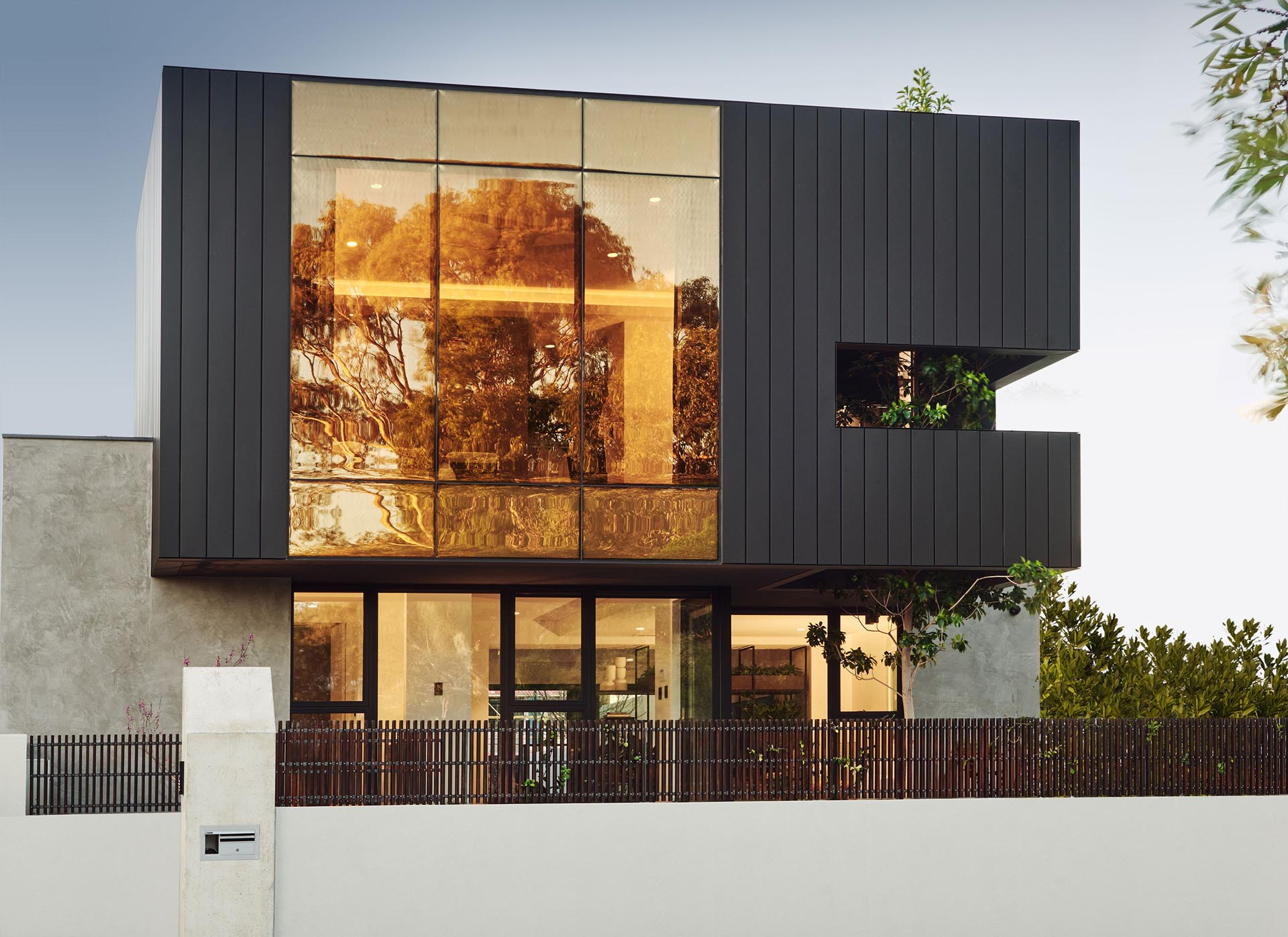 This modern home's facade features a superbronze, double glazed wall that's paired with matte siding.