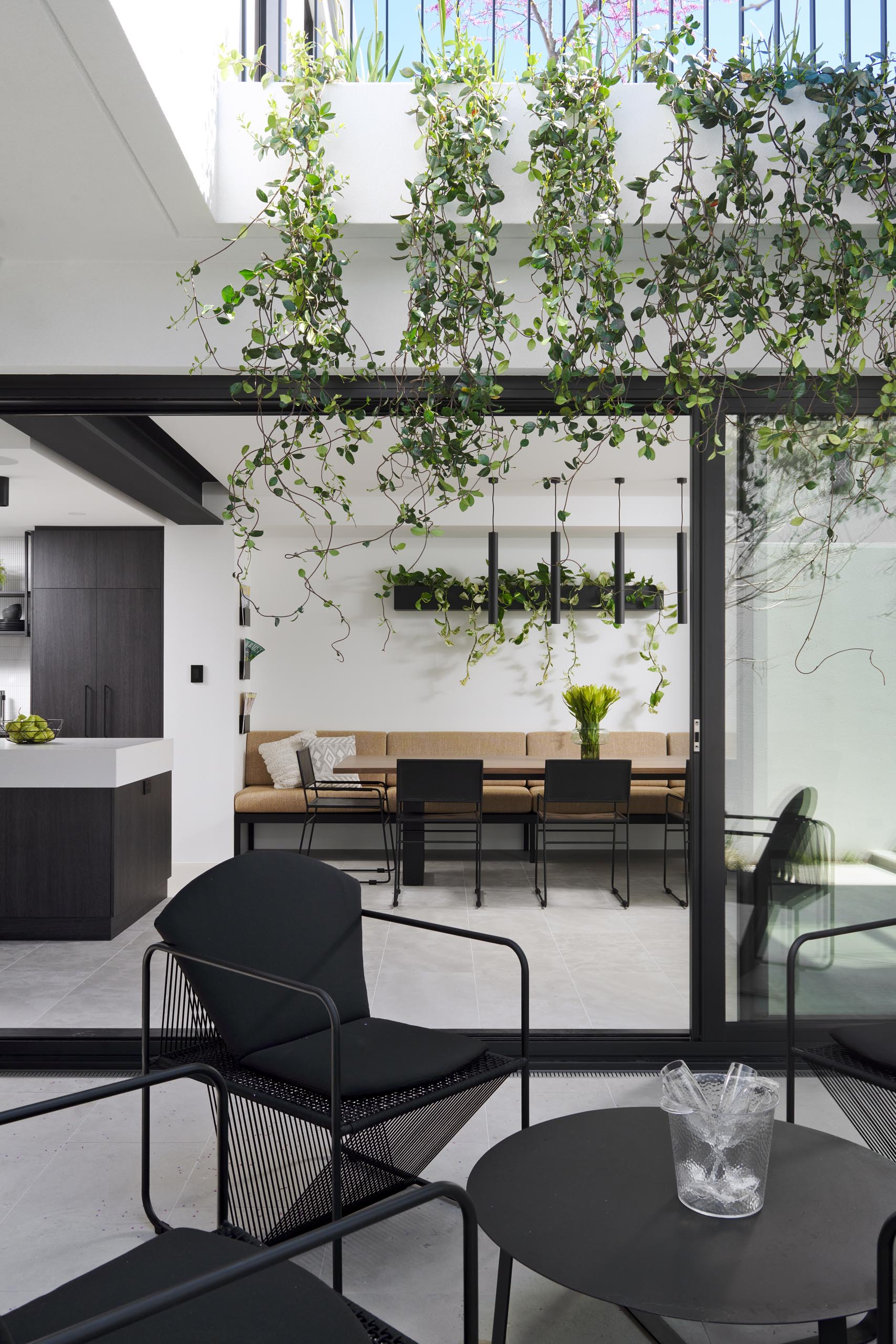 This modern dining room is adjacent to the kitchen and includes a long built-in banquette bench, a wall-mounted planter, and black dining chairs.