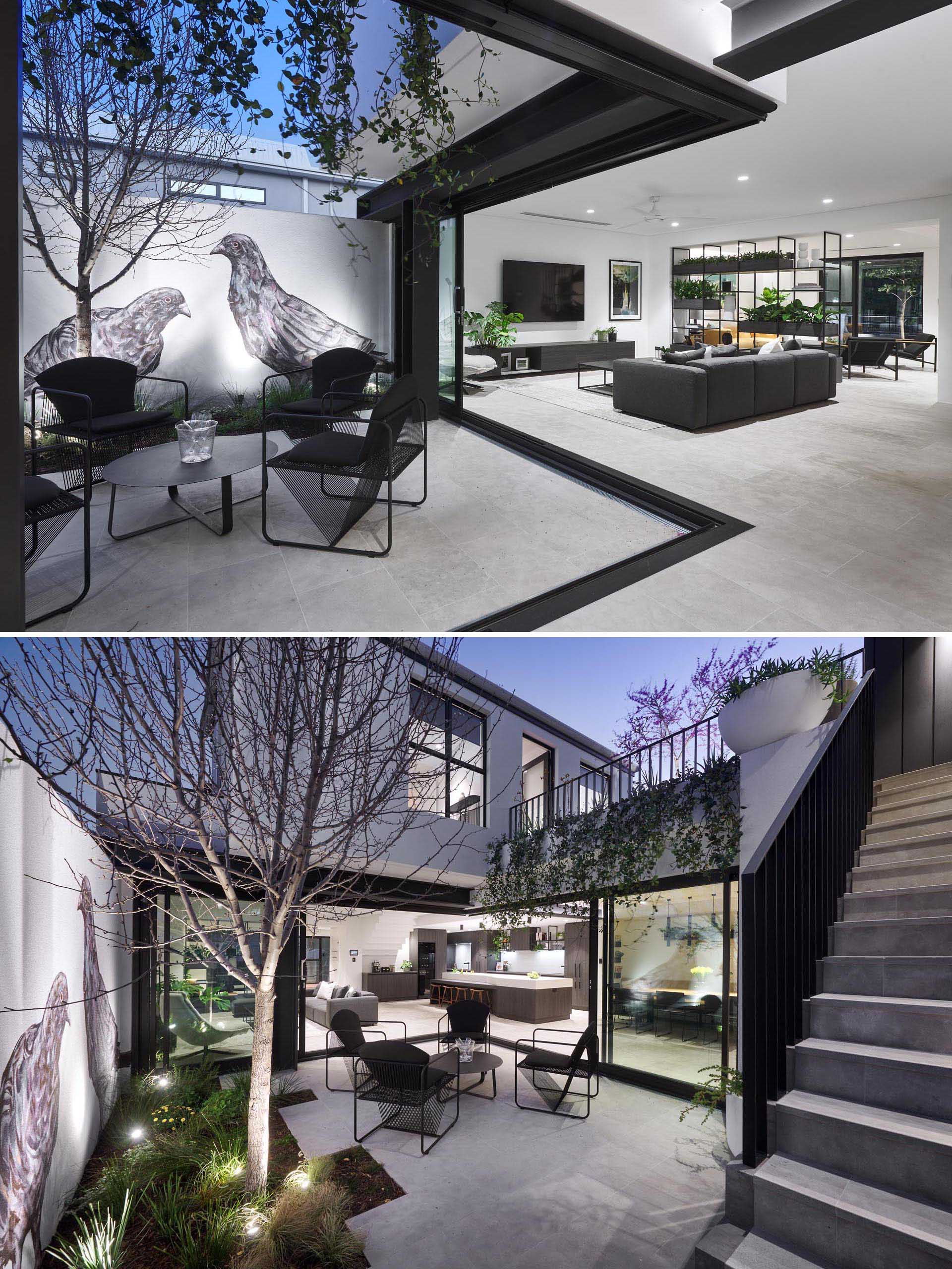 A modern house with a courtyard that's furnished with four sculptural chairs and a small round table. On the wall is a large mural of birds that adds an artistic touch to the space.