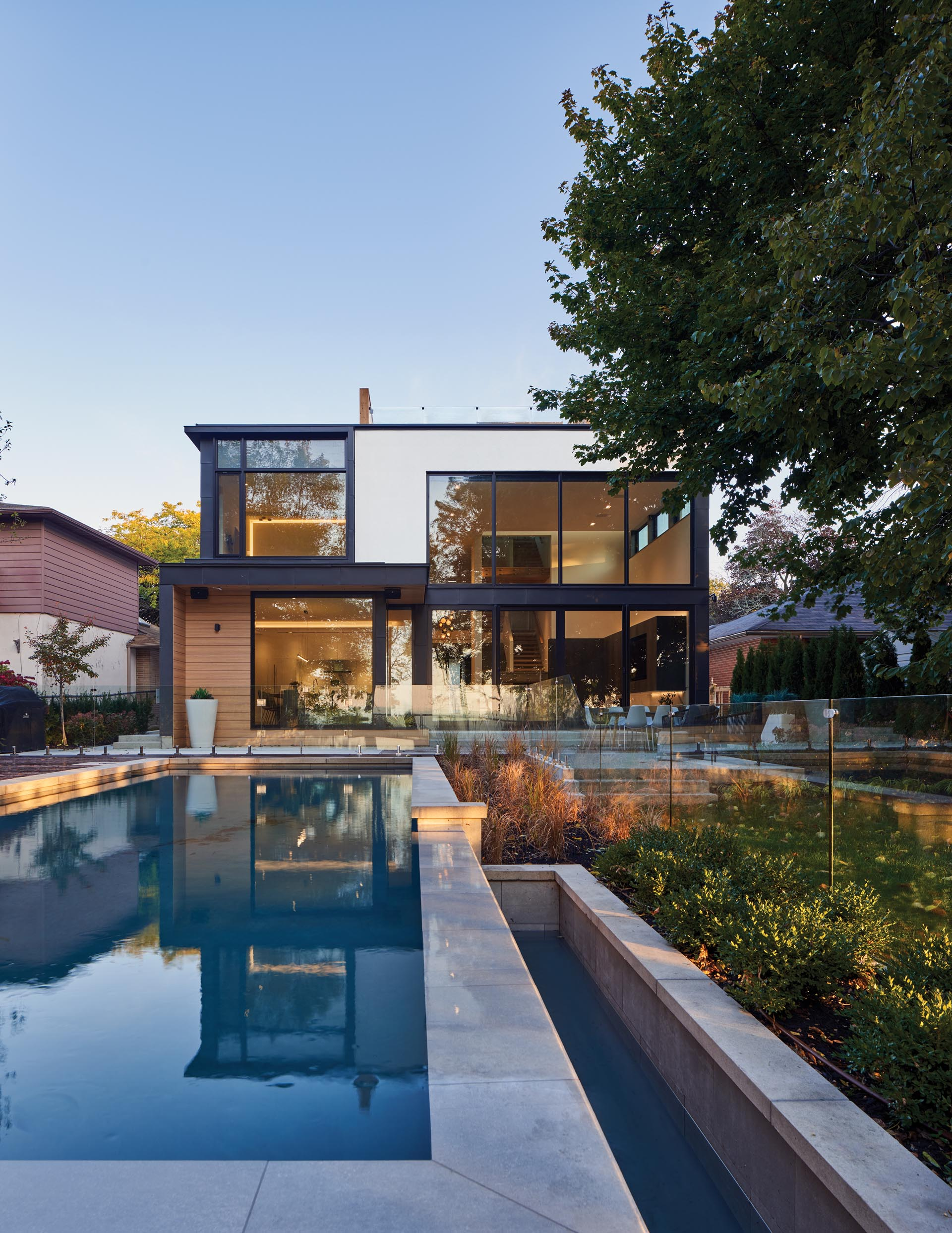 A modern house with double-height windows, a swimming pool, and a patio with room for outdoor dining.