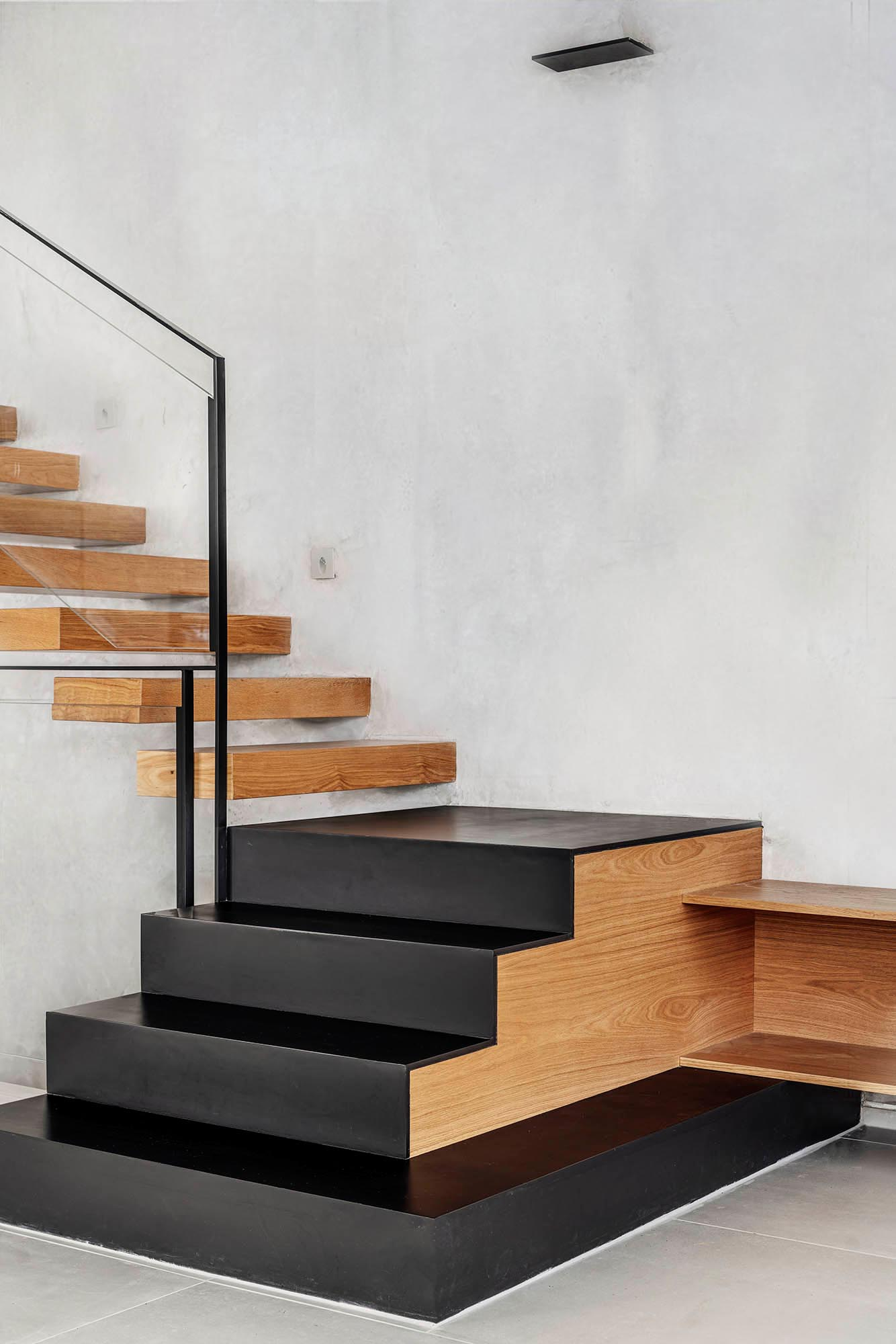 A floating oak staircase connects the various levels of this modern home, incorporates black iron stairs at the bottom, and transitions to become the TV sideboard in the living room.