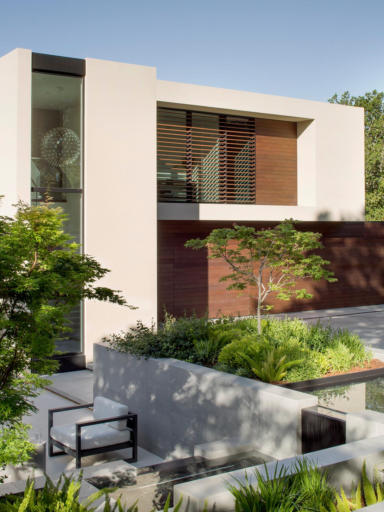 Much of the landscape around this modern house has been left to its natural state, however some areas have been updated to include water features, retaining walls, pathways, and small sitting areas.