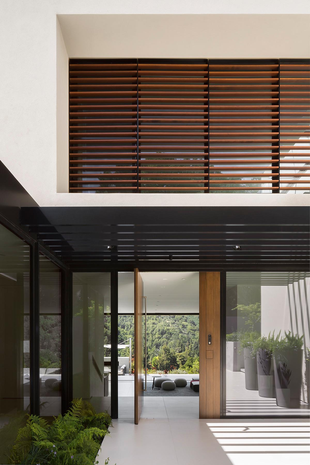 Upon arrival at this modern house, a sunken entry courtyard guides visitors to the oversized pivoting wood front door.