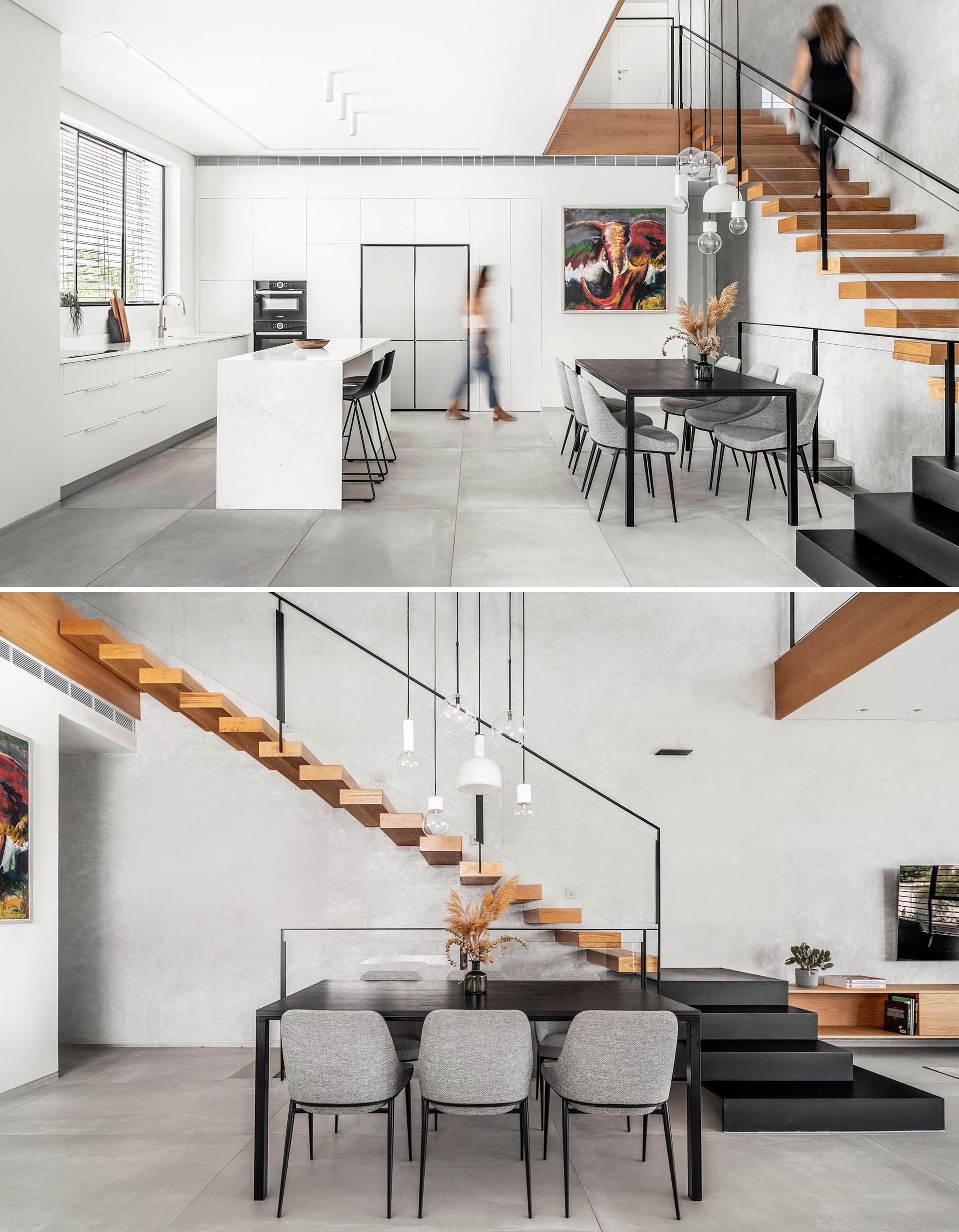 This modern dining room is furnished with a black table and light gray chairs, while white minimalist cabinets and drawers line the walls in the kitchen.