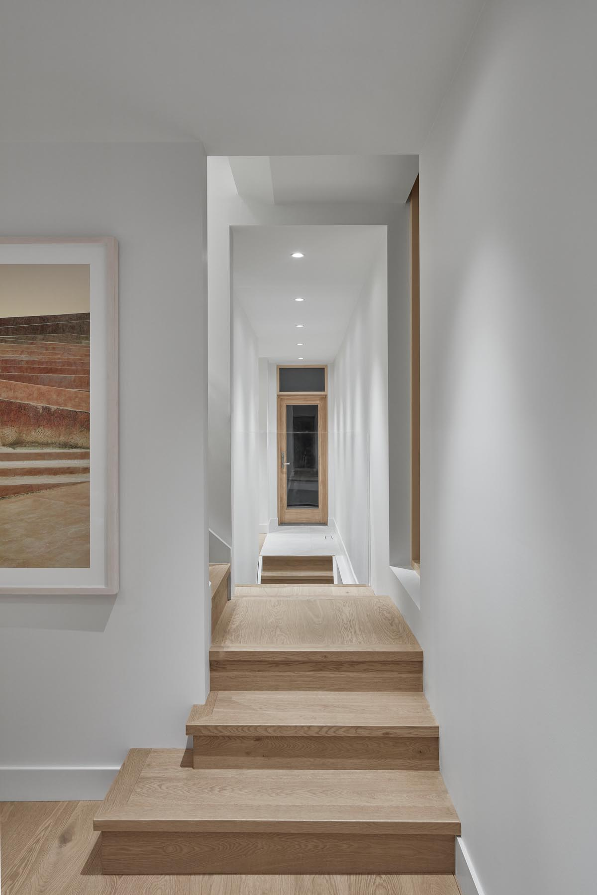 A modern hallway with wood floors, window frames, and doors.