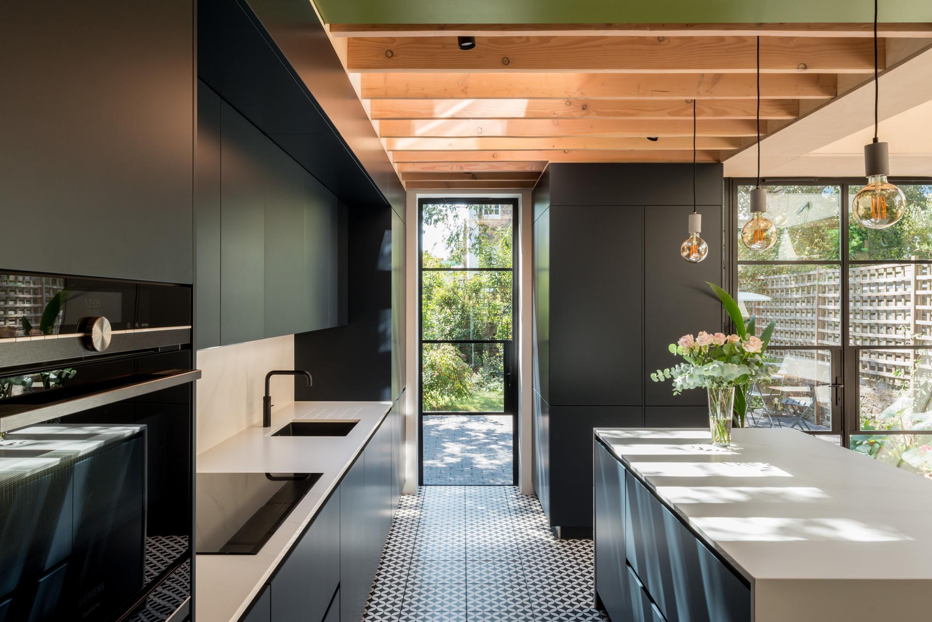 Minimalist matte black cabinets in this modern kitchen contrast the white countertops, while the patterned floor tile adds an artistic touch.
