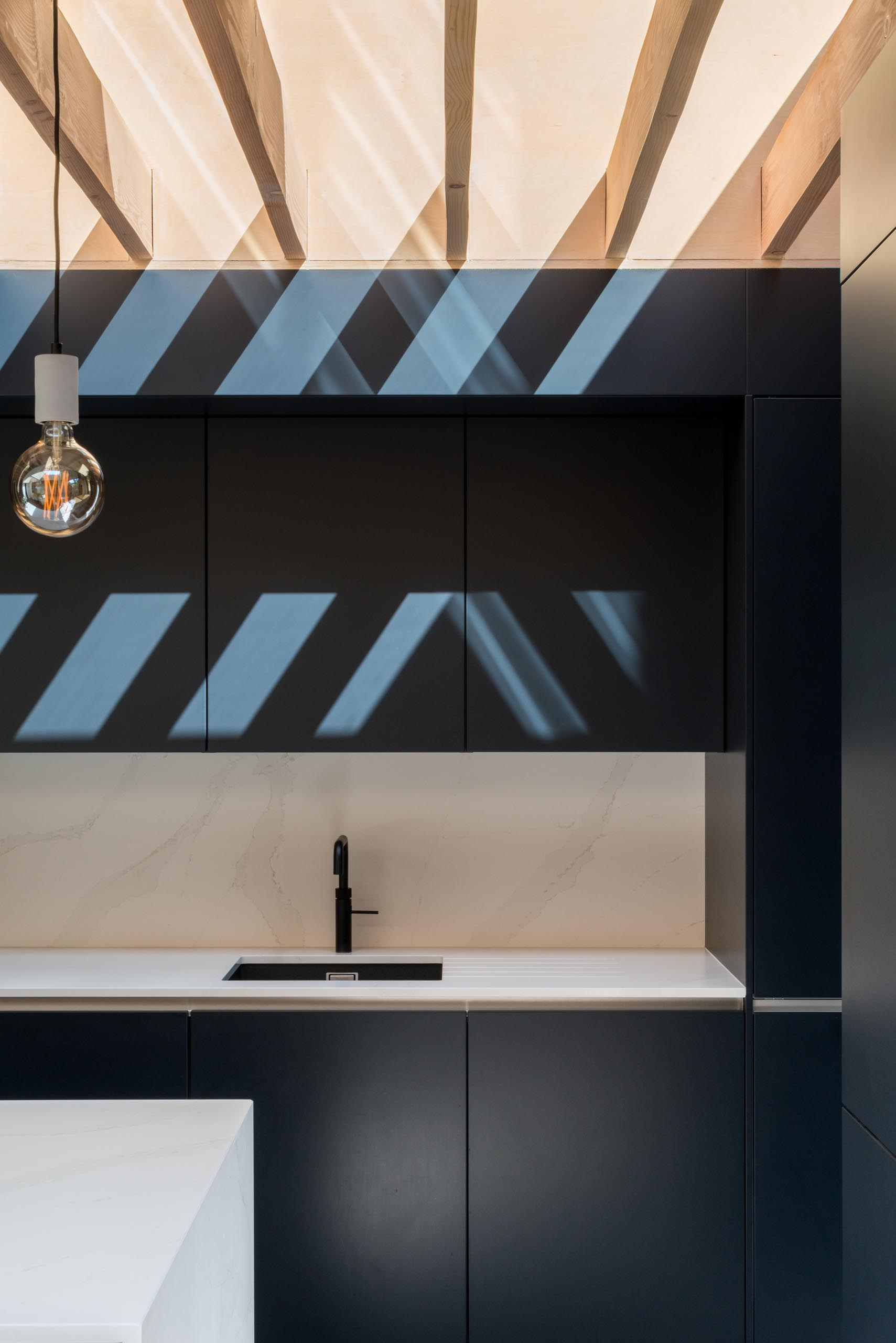 Modern matte black kitchen cabinets contrast the white countertops.