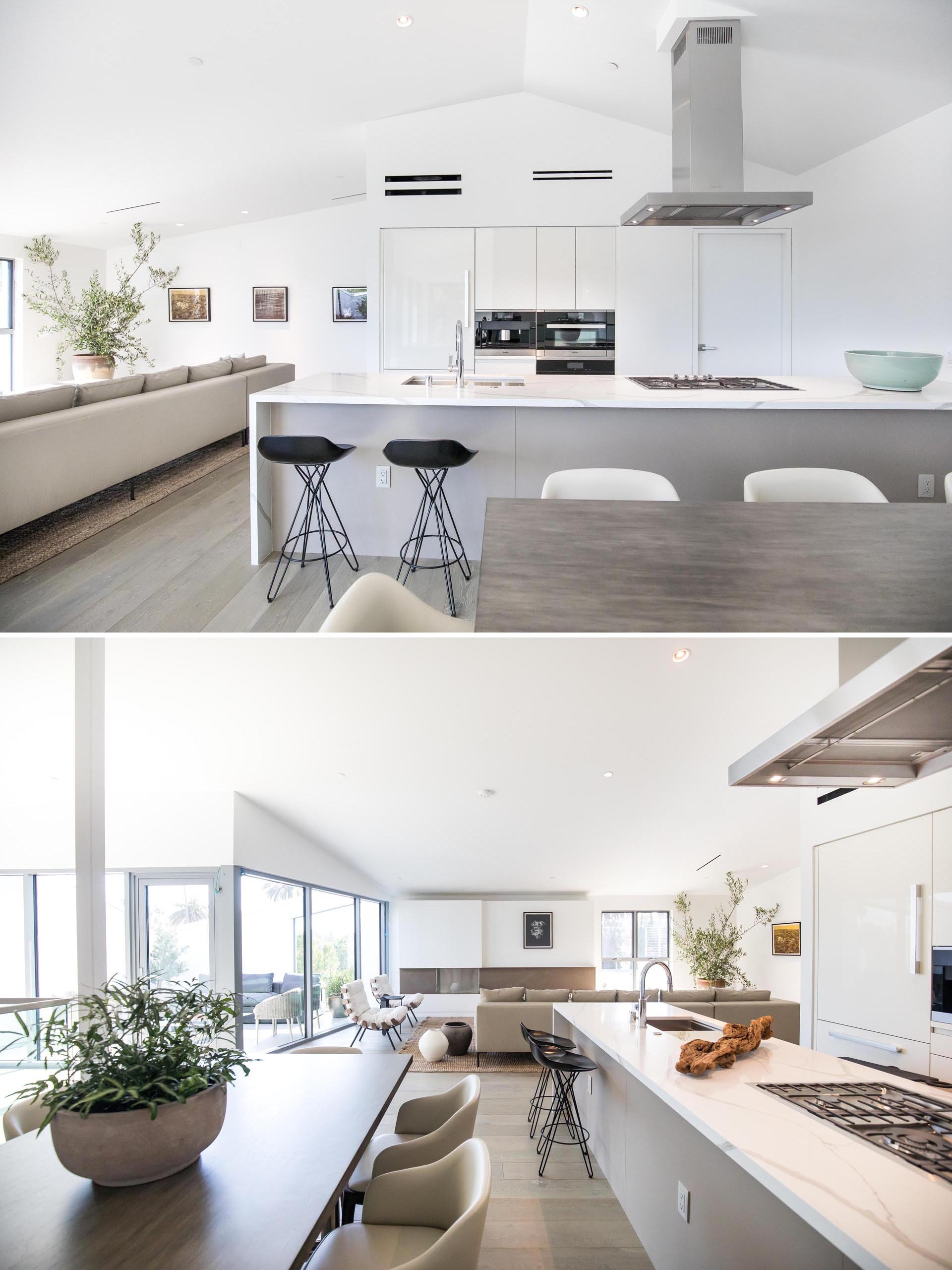 A modern plan open kitchen with white cabinets and white countertop.