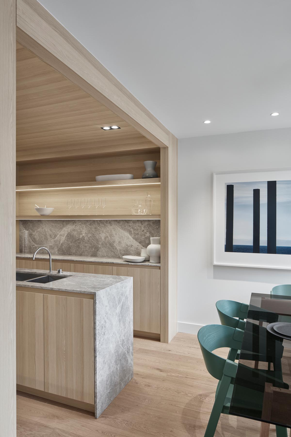 A modern kitchen with light wood cabinets, hidden lighting, and a long central island.